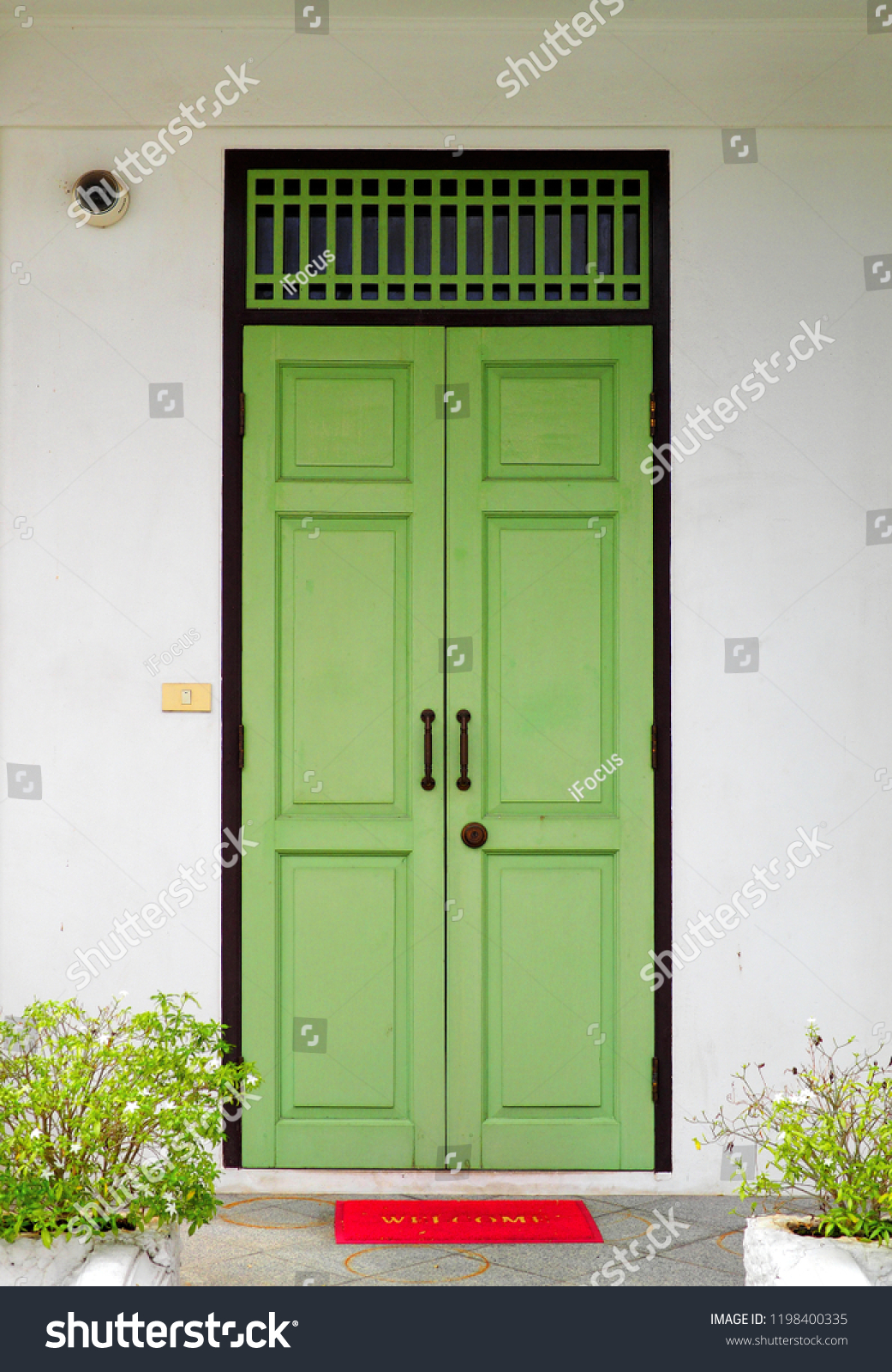 Closed green wooden doors with red welcome mat