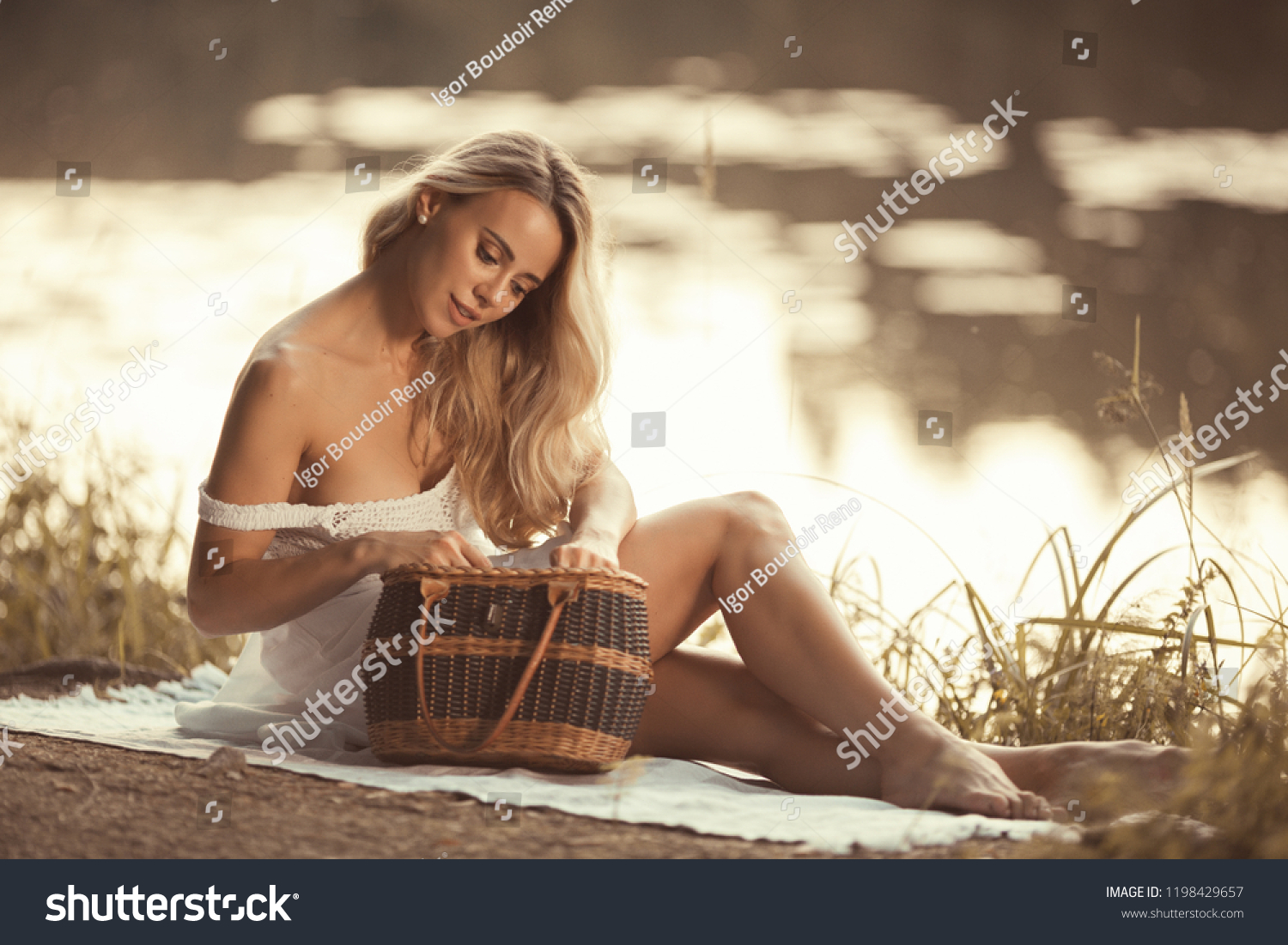 Sensual Young Woman With Beautiful Breasts And Shiny Long Blond Hair Sitting By The Lake At