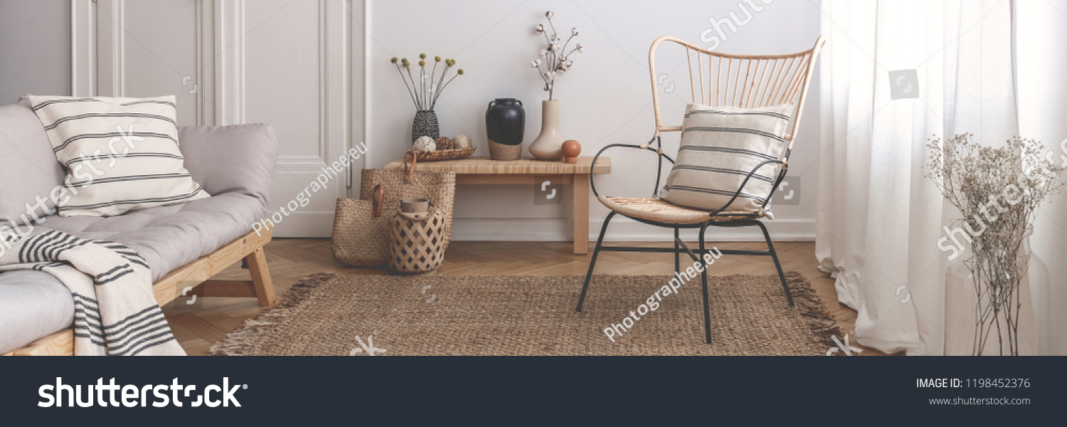 Panorama of armchair and grey sofa in natural living room interior with flowers. Real photo #1198452376