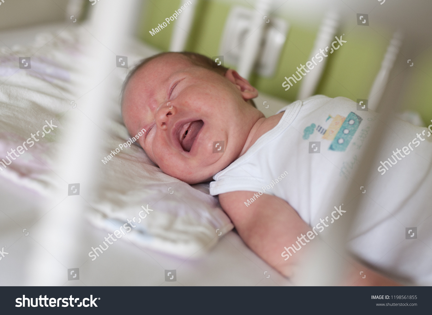 Crying newborn baby girl in crib