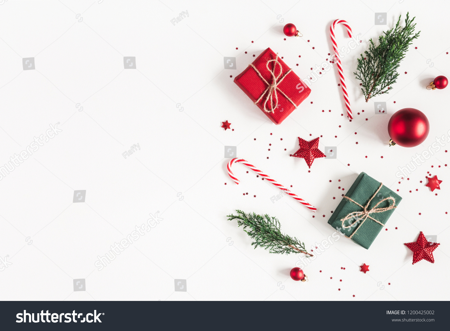 Christmas composition. Gifts, fir tree branches, red decorations on white background. Christmas, winter, new year concept. Flat lay, top view, copy space #1200425002