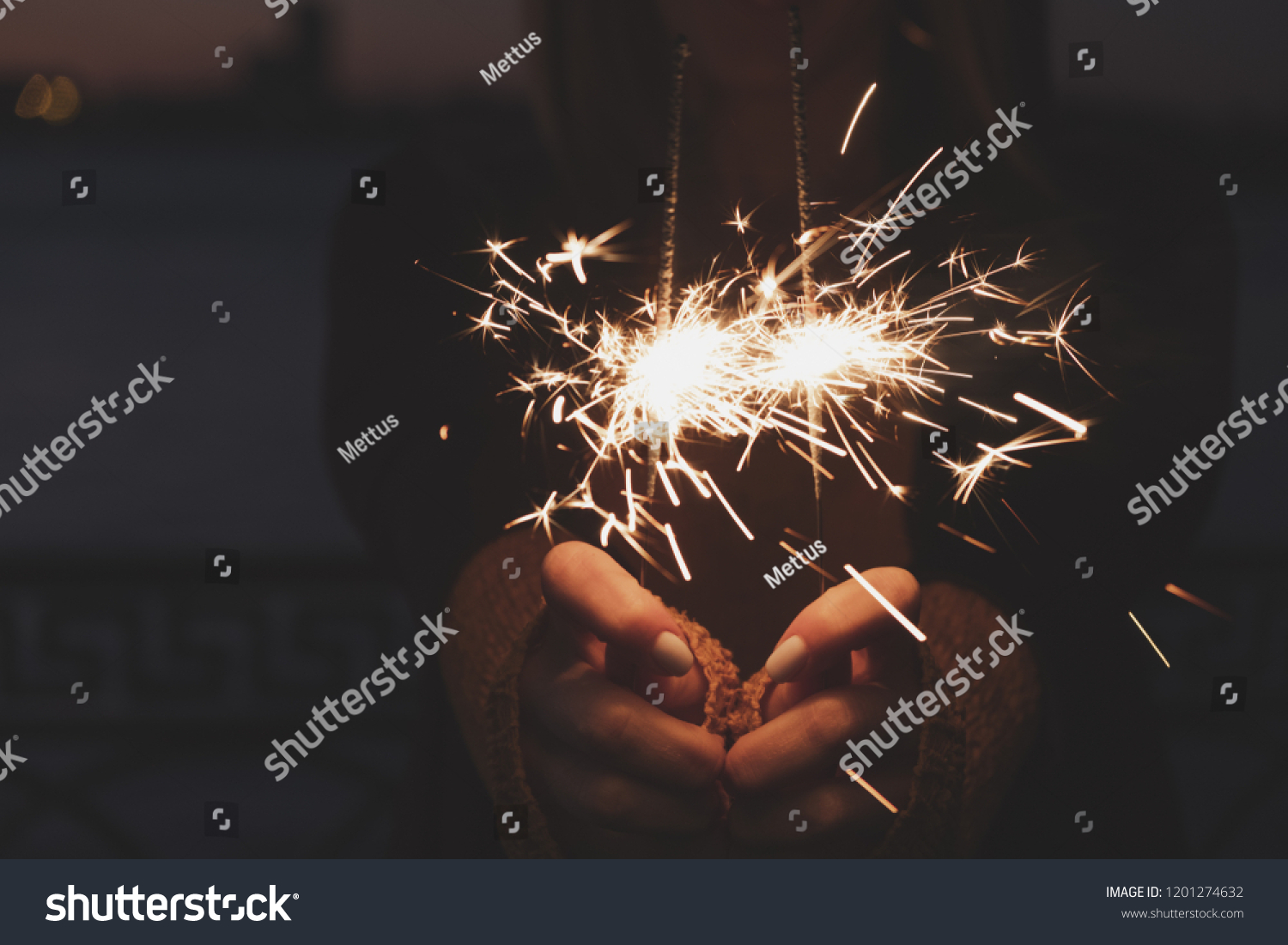 Female hands holding two burning sparklers in front of middle part of the body