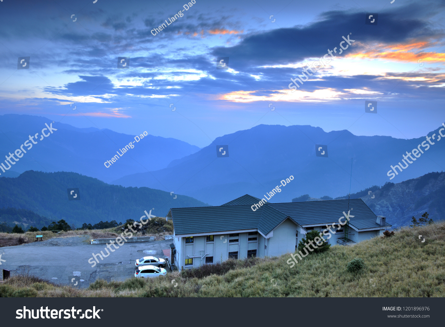 On the high mountains of the continuous mountains, the blue roofs of the white walls of the building, the blue sky has orange clouds. #1201896976