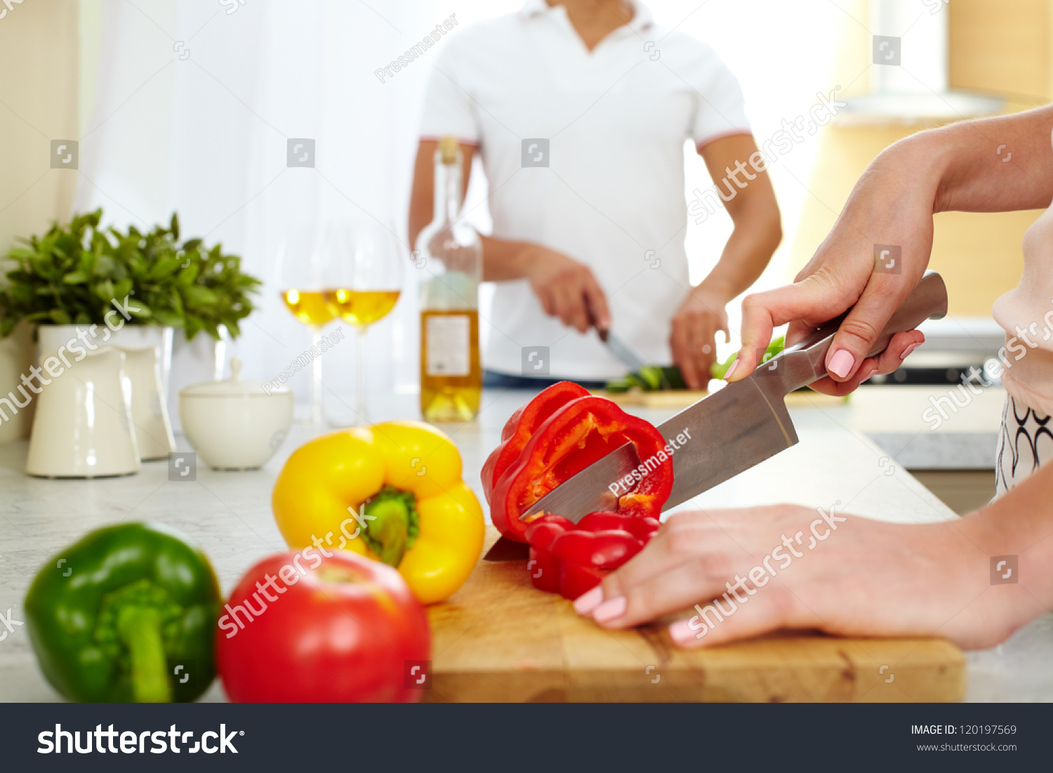 Close Up Of Young Female Cutting Red Pepper In The Kitchen