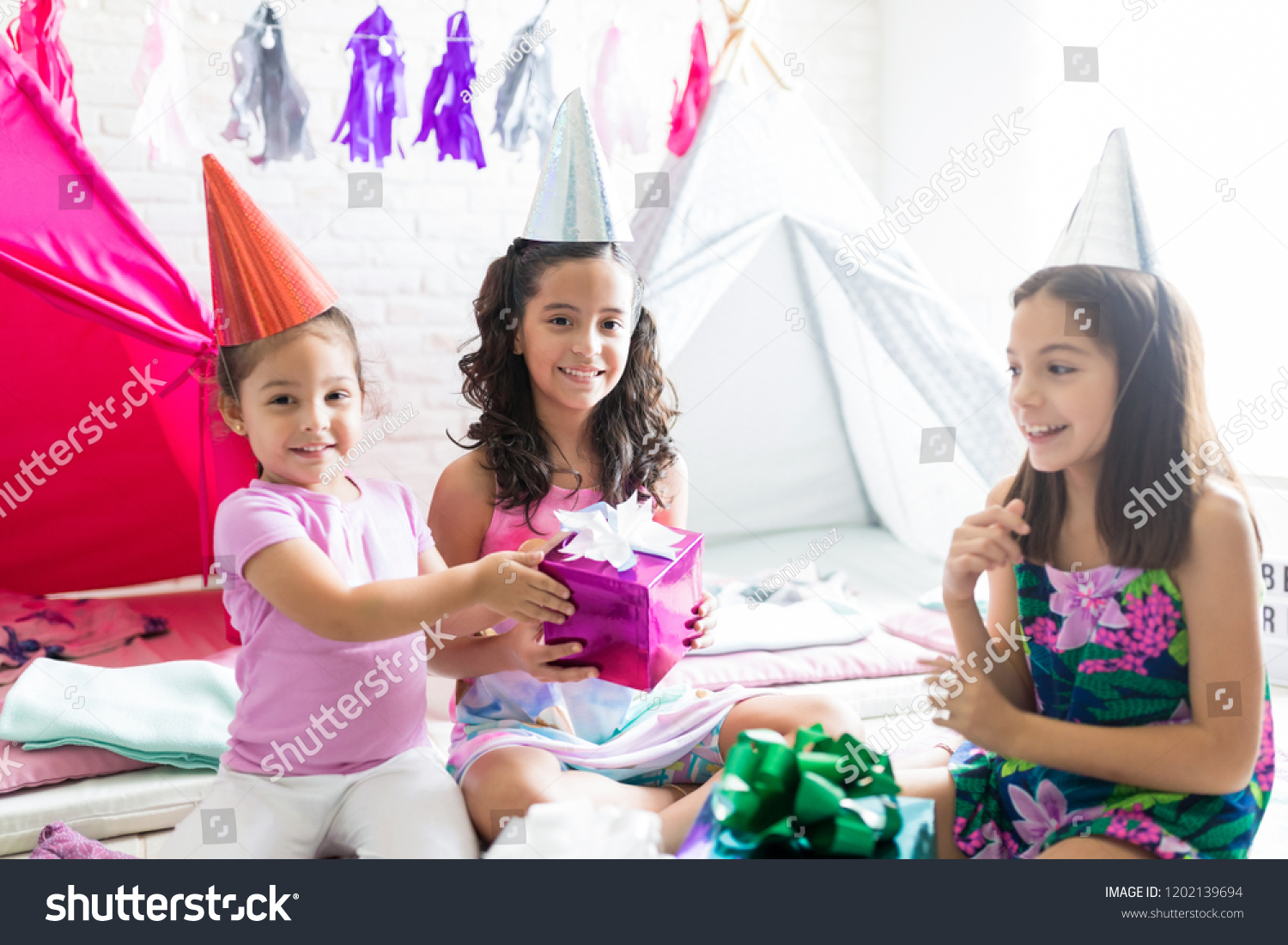 Happy Little Girl Giving Birthday Present To Friend During Pajama Party At Home