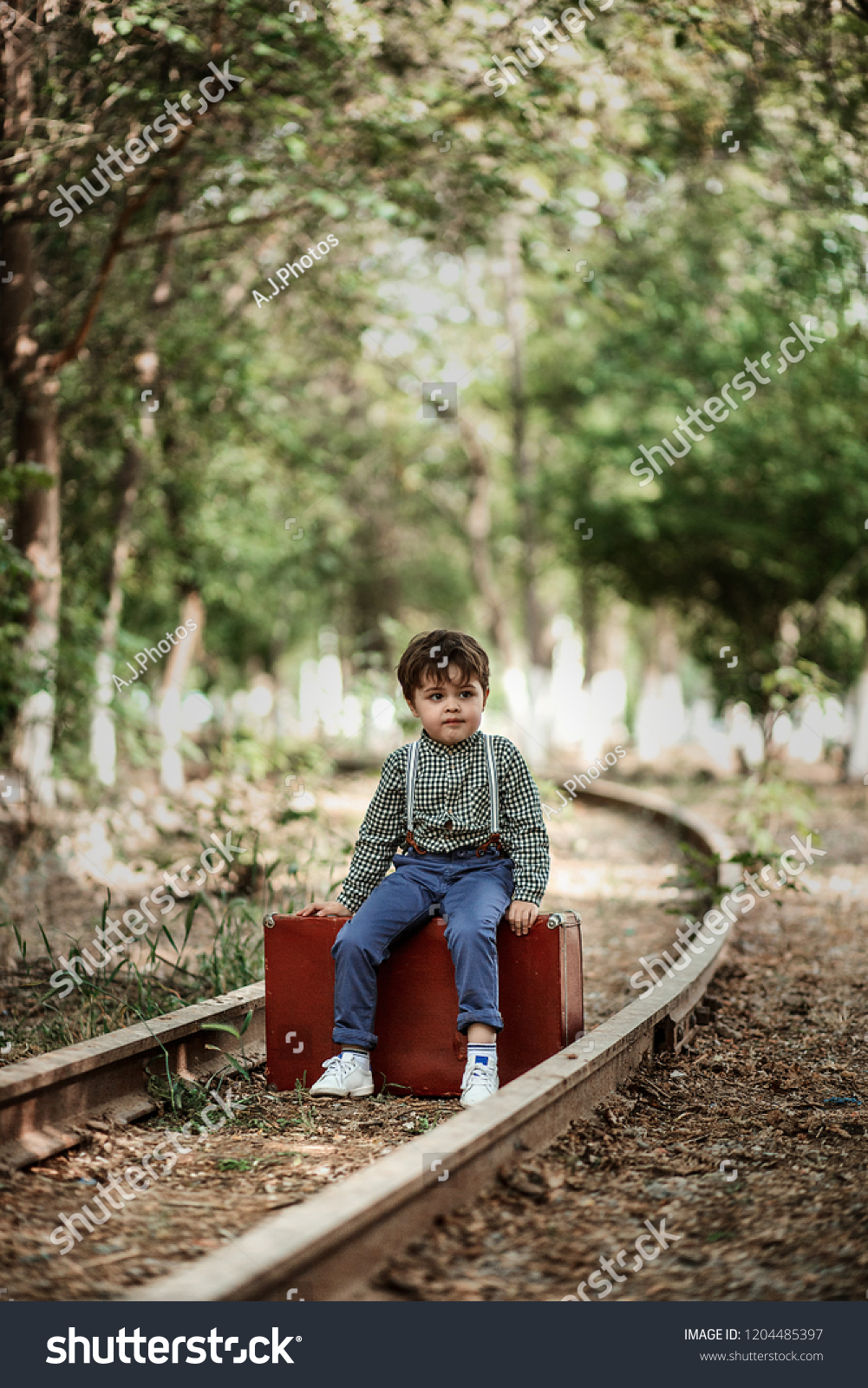 little cute boy in vintage clothes on a retro suitcase.