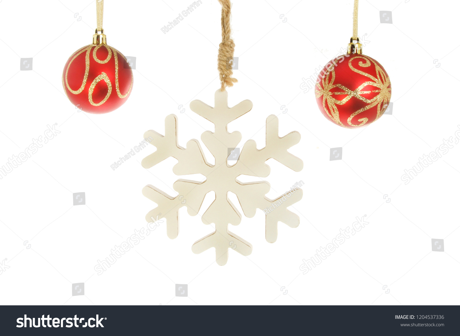 a0116d93f0e7 Christmas decorations, red and gold glitter baubles hanging with a  snowflake decoration isolated against white