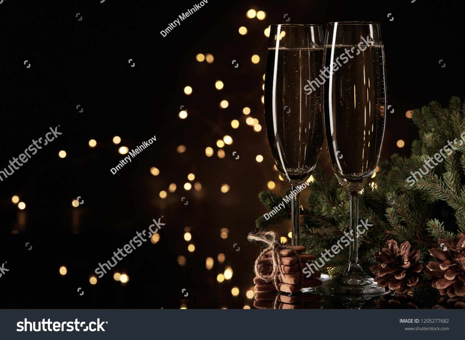 Two glasses with champange, fir tree branch and gingerbread cookies on a dark background with LED lights garland. New year and Christmas. #1205277682