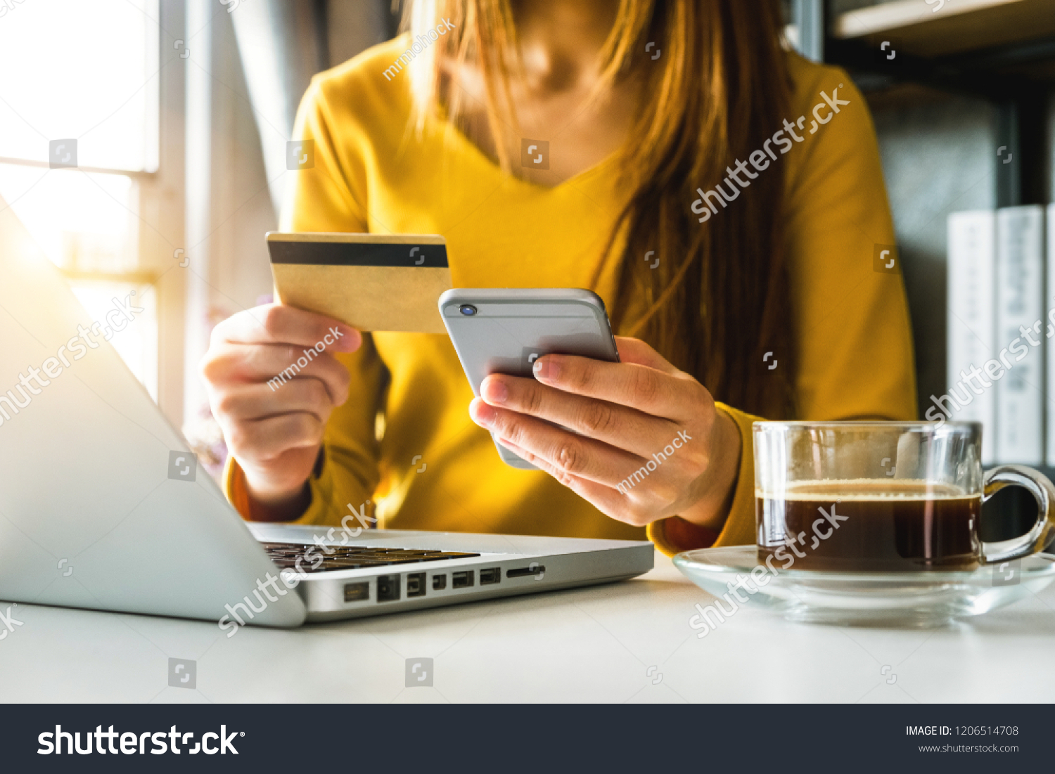businesswoman hand using smart phone, tablet payments and holding credit card online shopping, omni channel, digital tablet docking keyboard computer at office in sun light  #1206514708