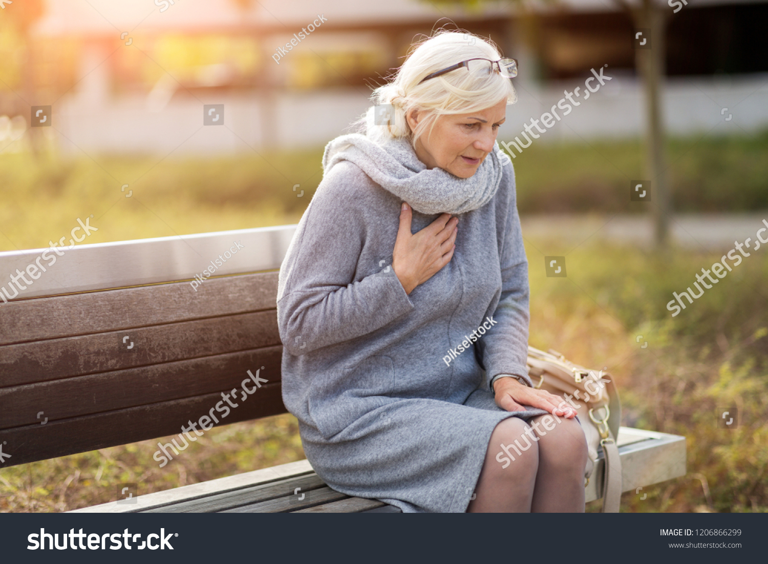 Senior Woman Suffering From Chest Pain While Sitting On Bench #1206866299