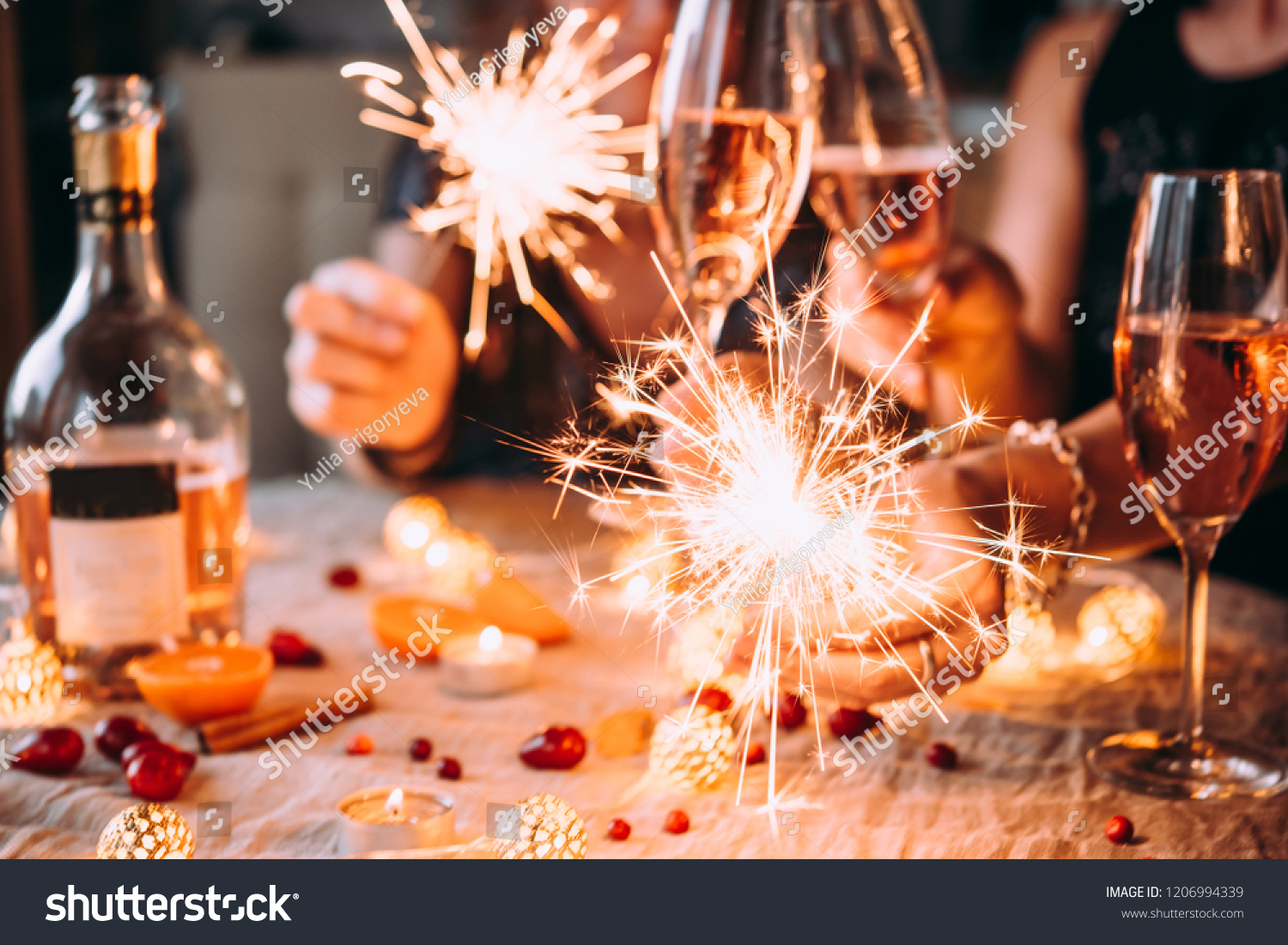 Friends celebrating Christmas or New Year eve party with Bengal lights and rose champagne. #1206994339