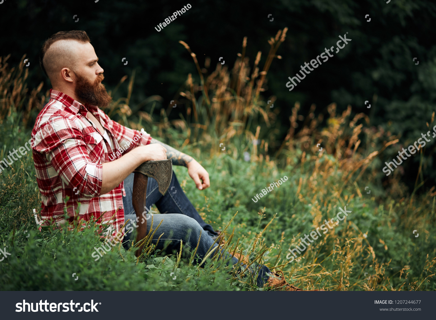 54c31f878d9 brutal lumberjack in red shirt with beard holding axe sitting in Forest  after work