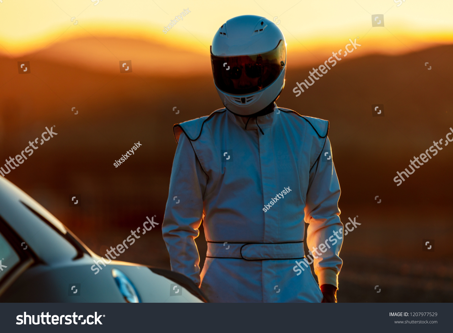 A Helmet Wearing Race Car Driver In The Early Morning Sun Looking At His Car Before Starting #1207977529
