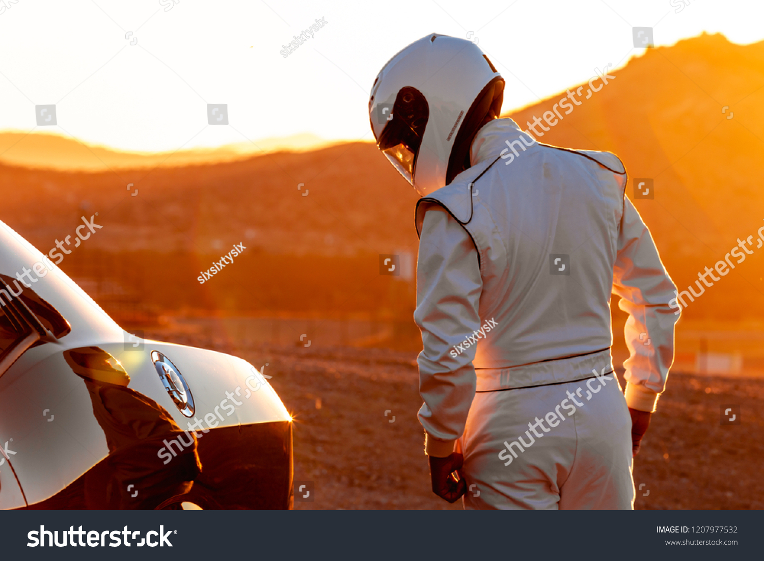 A Helmet Wearing Race Car Driver In The Early Morning Sun Looking At His Car Before Starting #1207977532