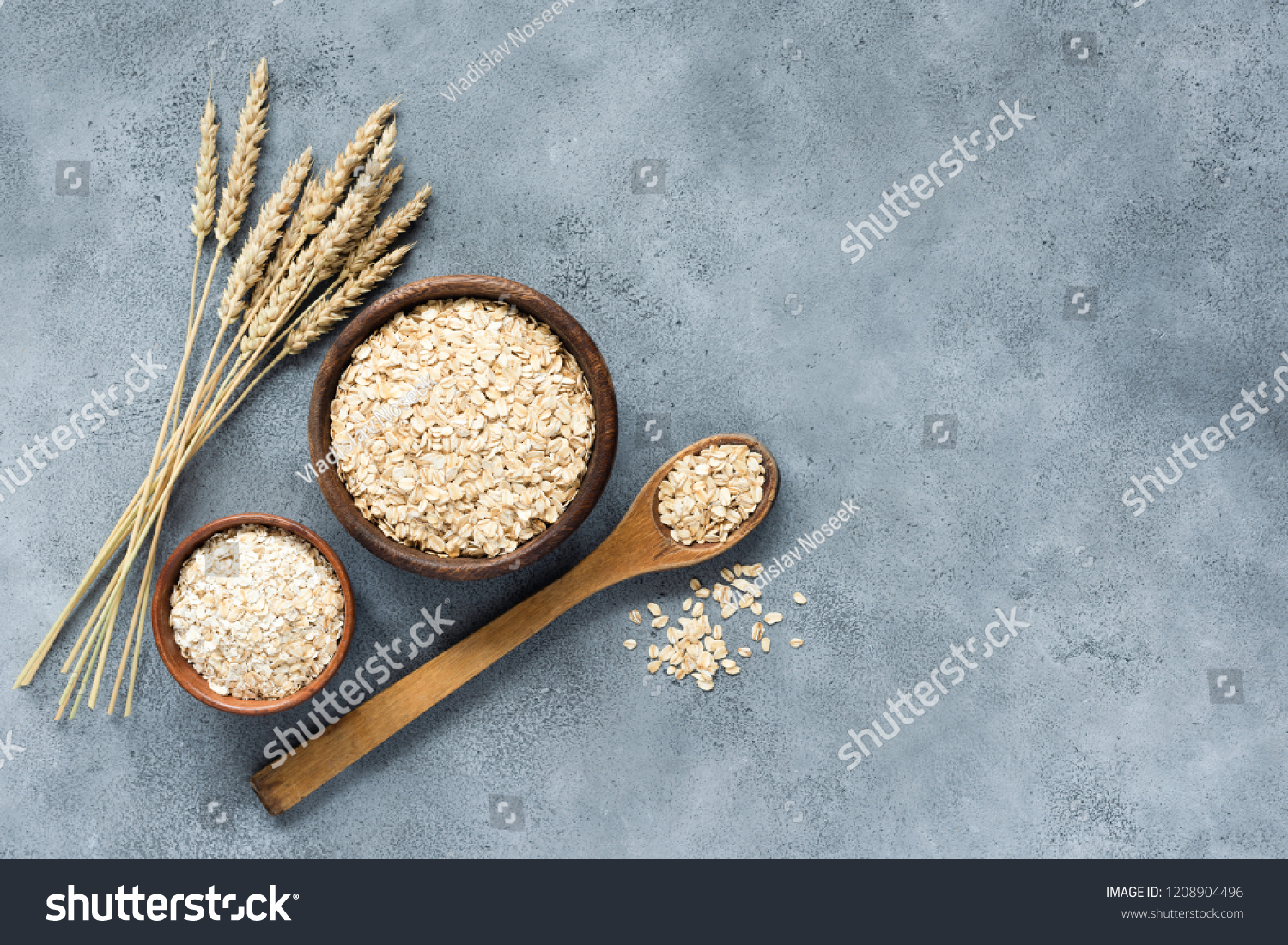 Oats, rolled oats and oat flakes in wooden bowl, top view. Concept of healthy eating, healthy lifestyle, dieting and vegetarian food #1208904496