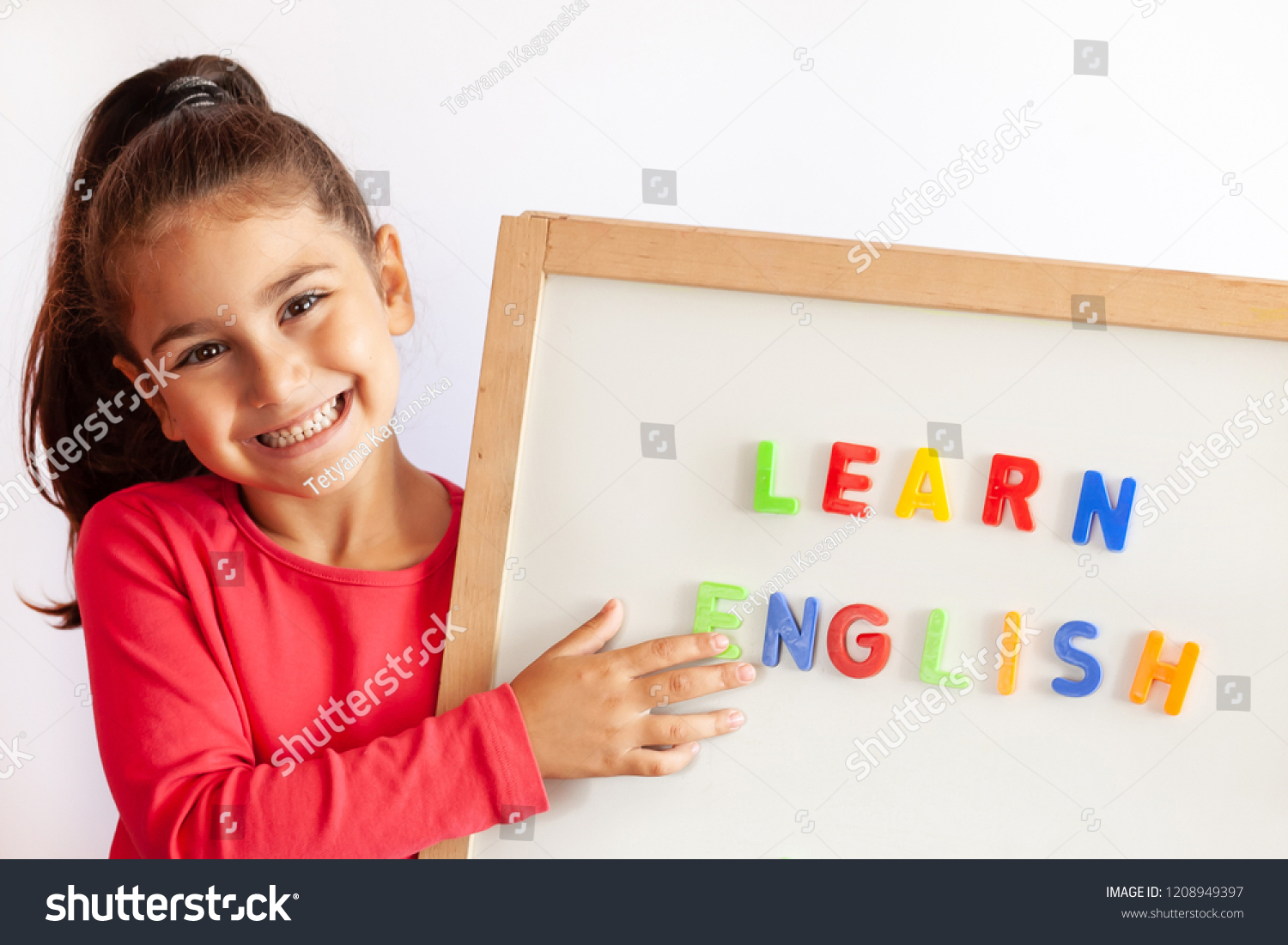 Language education concept. Learn English. Do you speak English. Cute little child girl with letters on the blackboard. English language school. English for children. #1208949397
