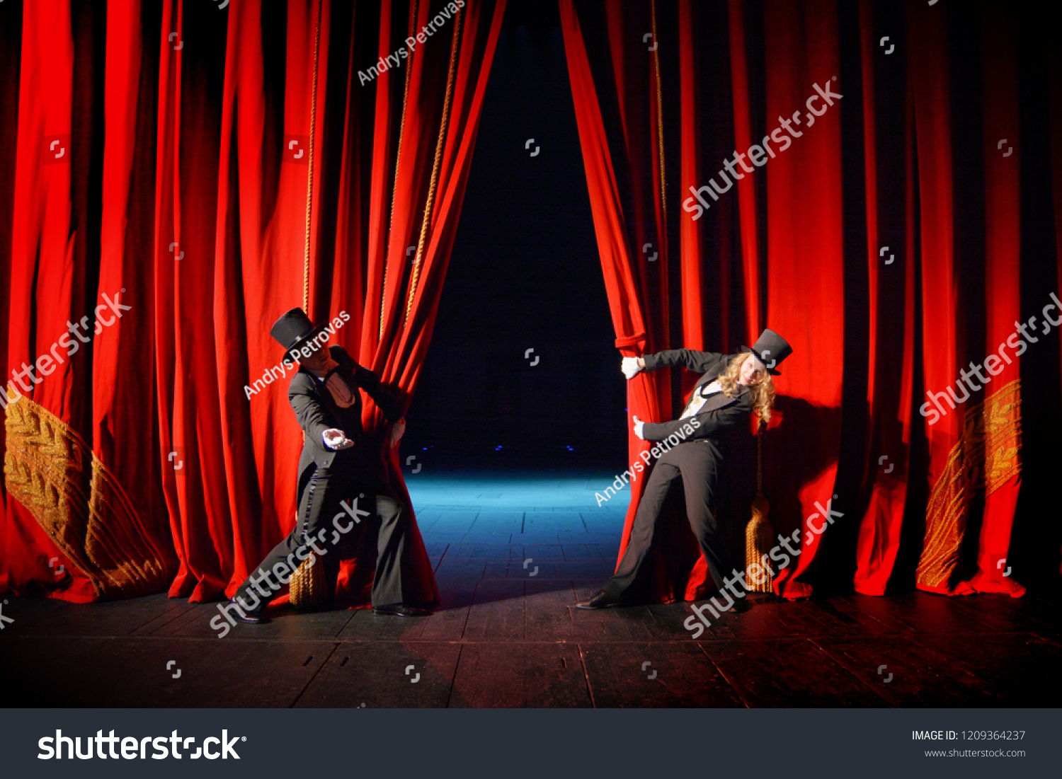 Actor and actress in tuxedos open theater curtain #1209364237