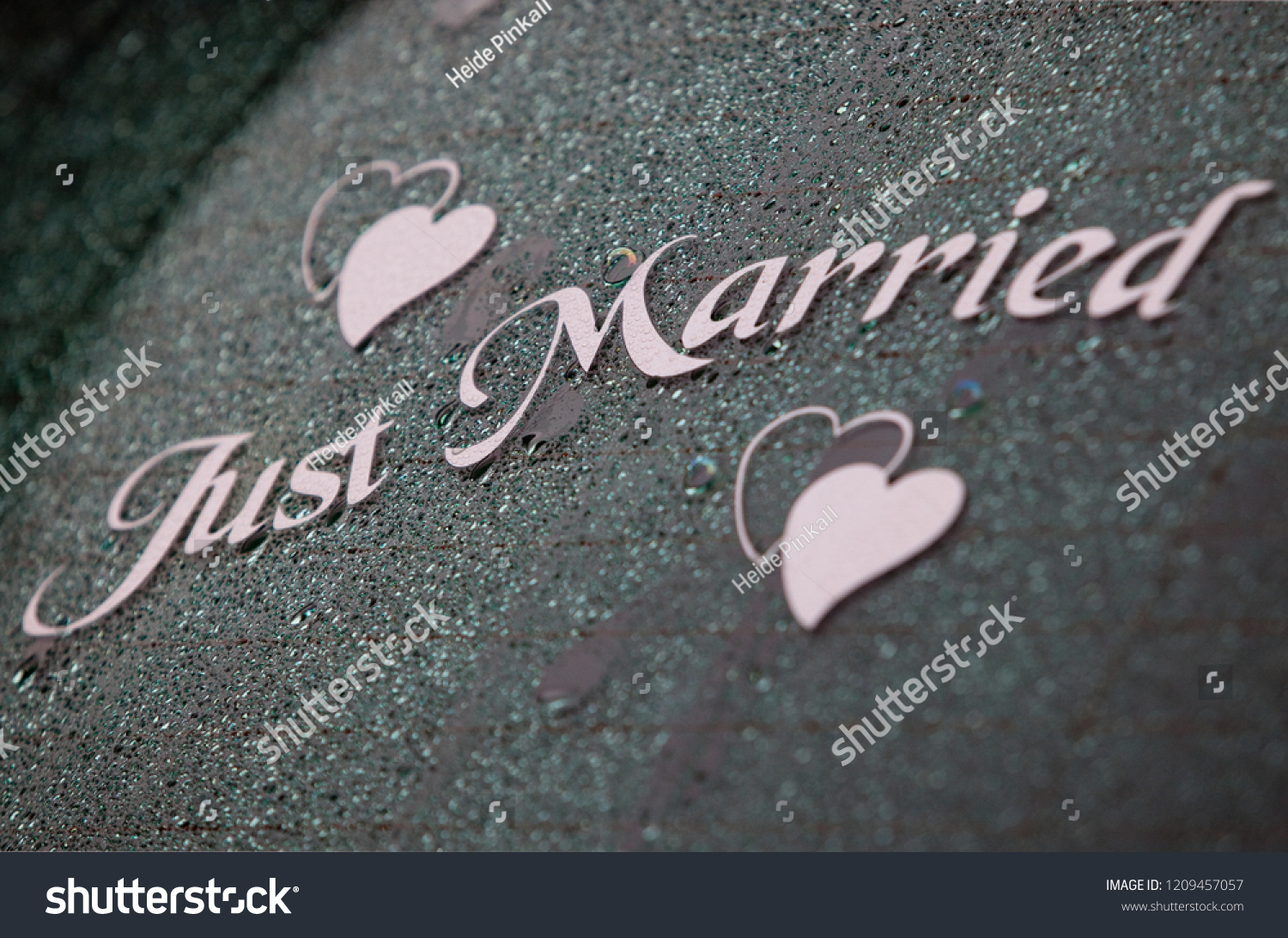 The words just married in elegant light pink letters with two heart shape stickers