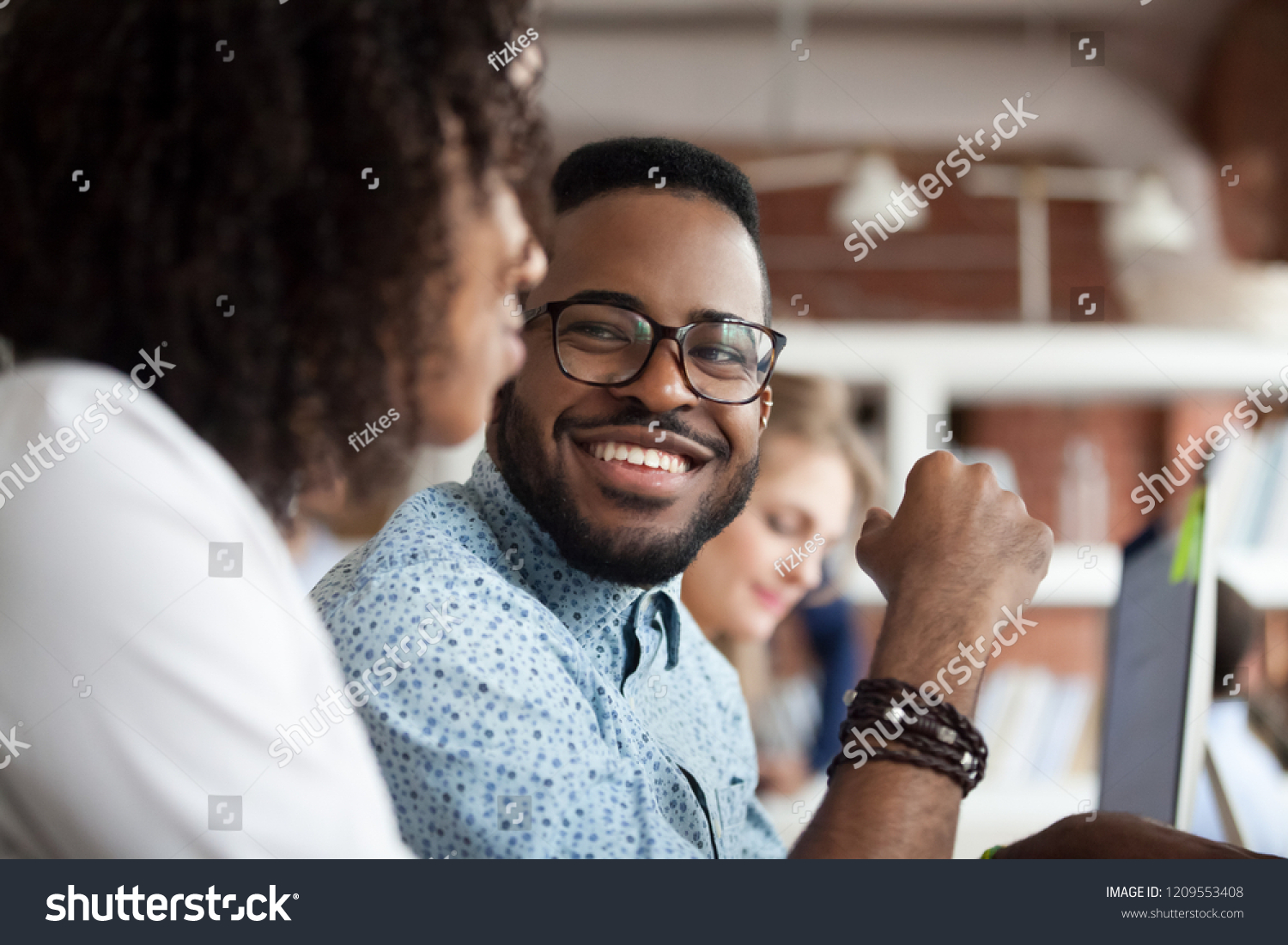 Close up of smiling African American employee look at female colleague chatting in office, happy black male worker talk with woman coworker, having casual conversation at workplace, have fun #1209553408