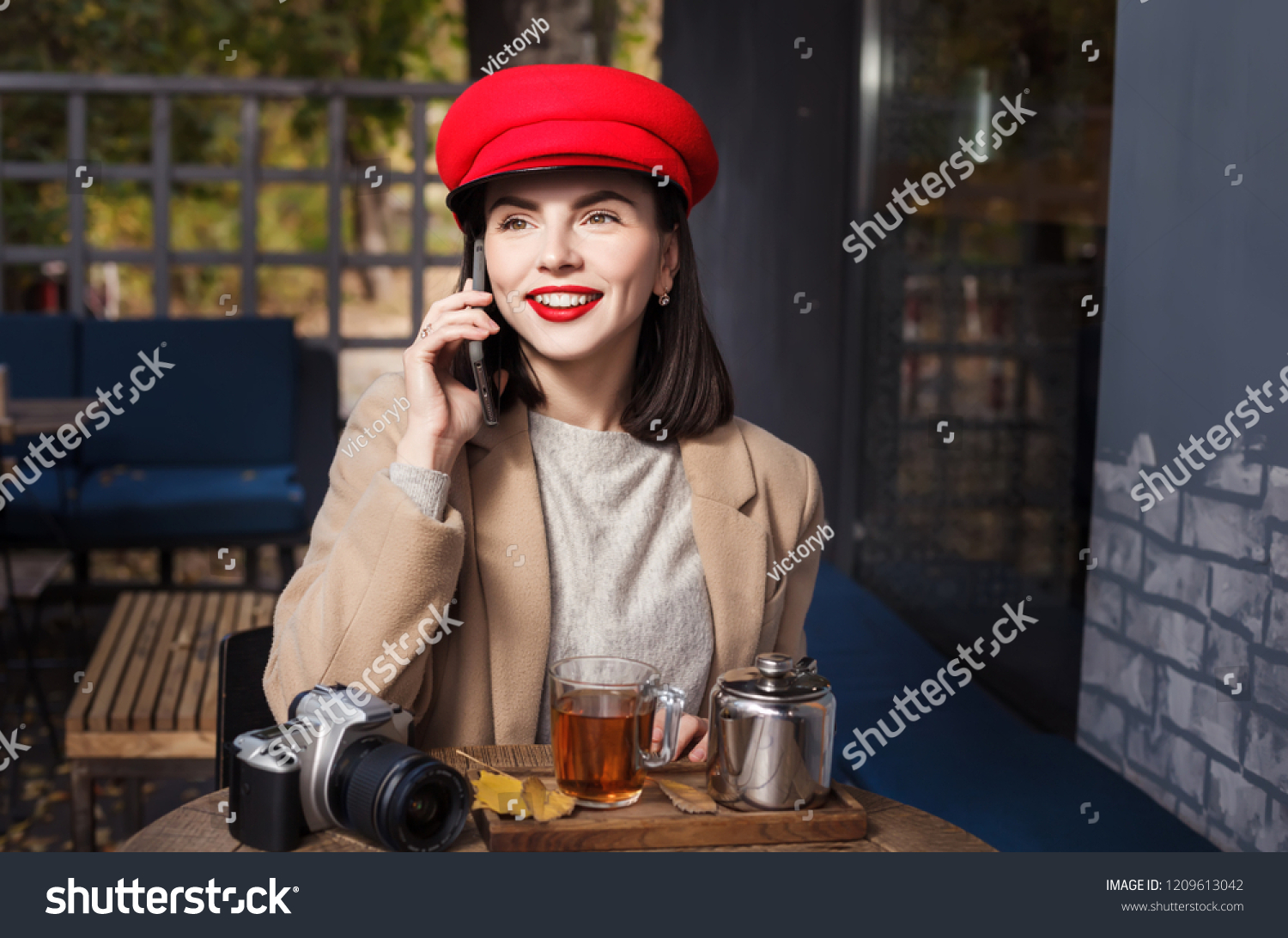 Young beautiful girl is drinking tea and talking on the phone in a cafe #1209613042