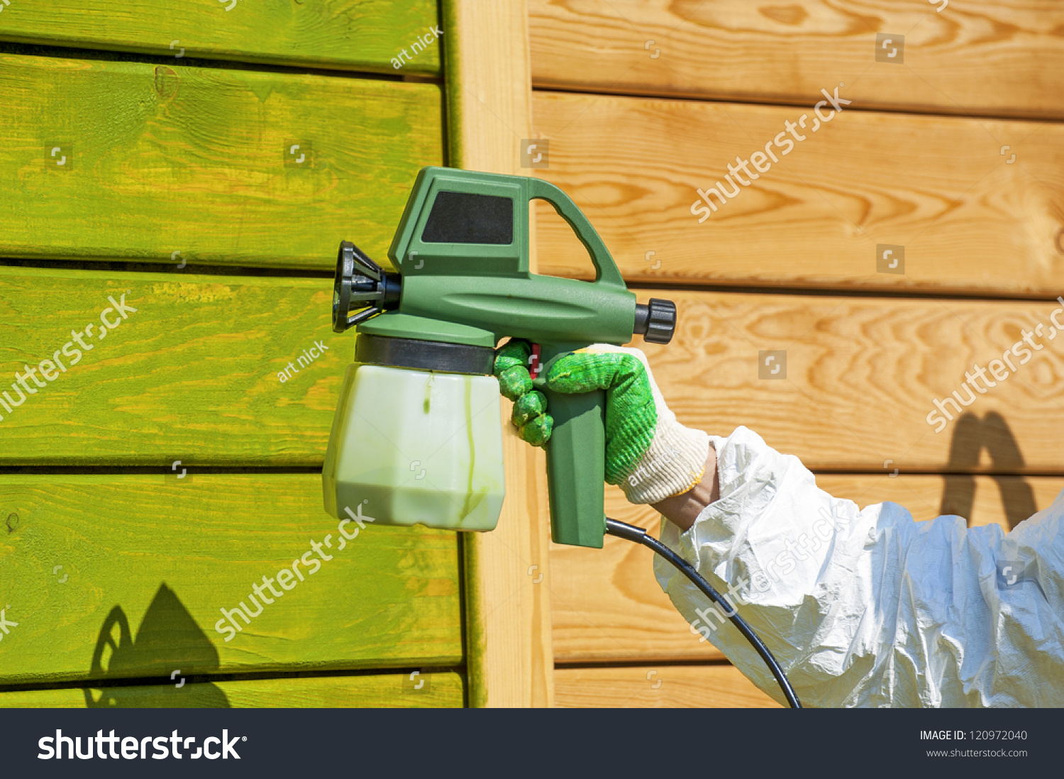 hand painting wooden wall with spray gun in green stock photo. Black Bedroom Furniture Sets. Home Design Ideas