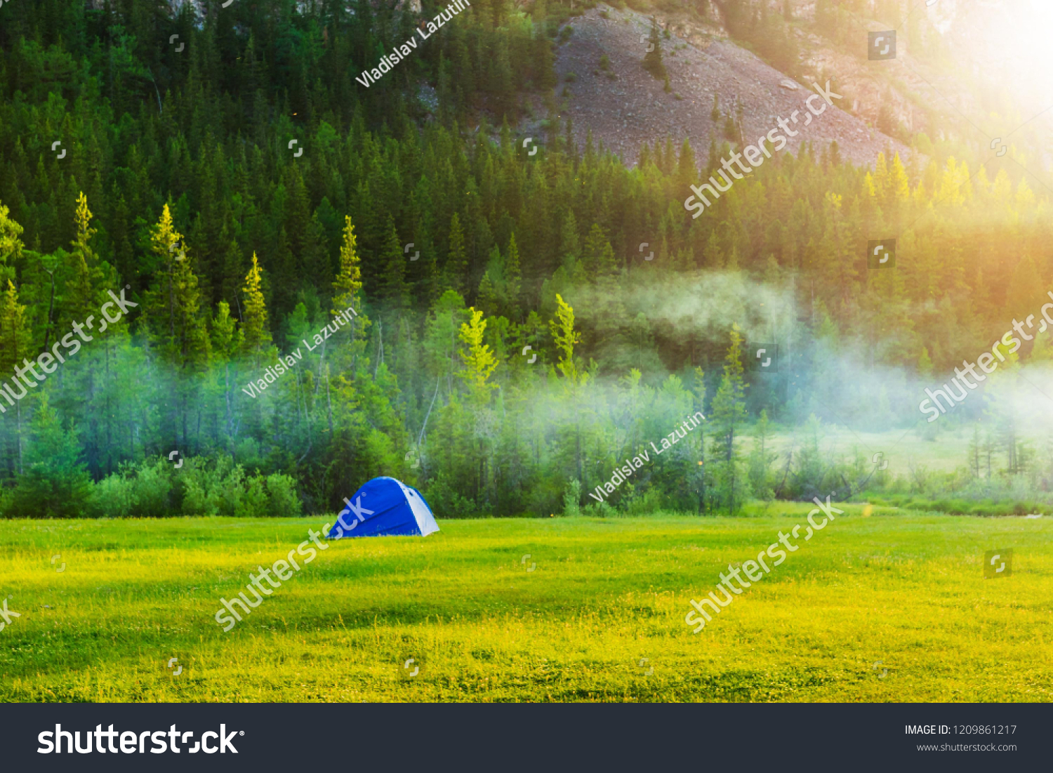 Tourist tent at the foot of the mountains. Camping on the grass near the mountain in the rays of the evening sun. Mountain landscape and sunset. #1209861217
