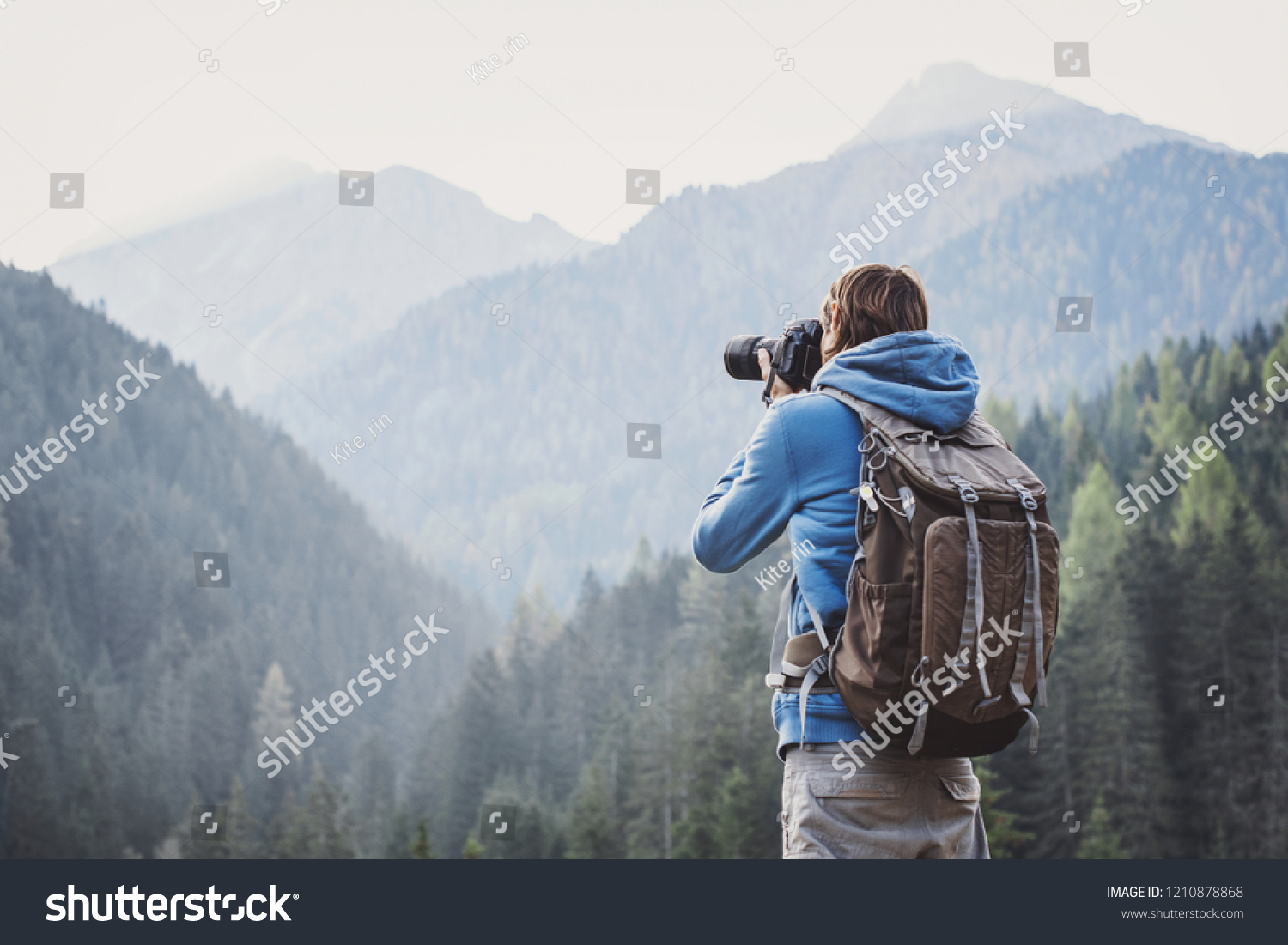 Young cheerful man photographer taking photographs with digital camera in a mountains. Travel and active lifestyle concept #1210878868