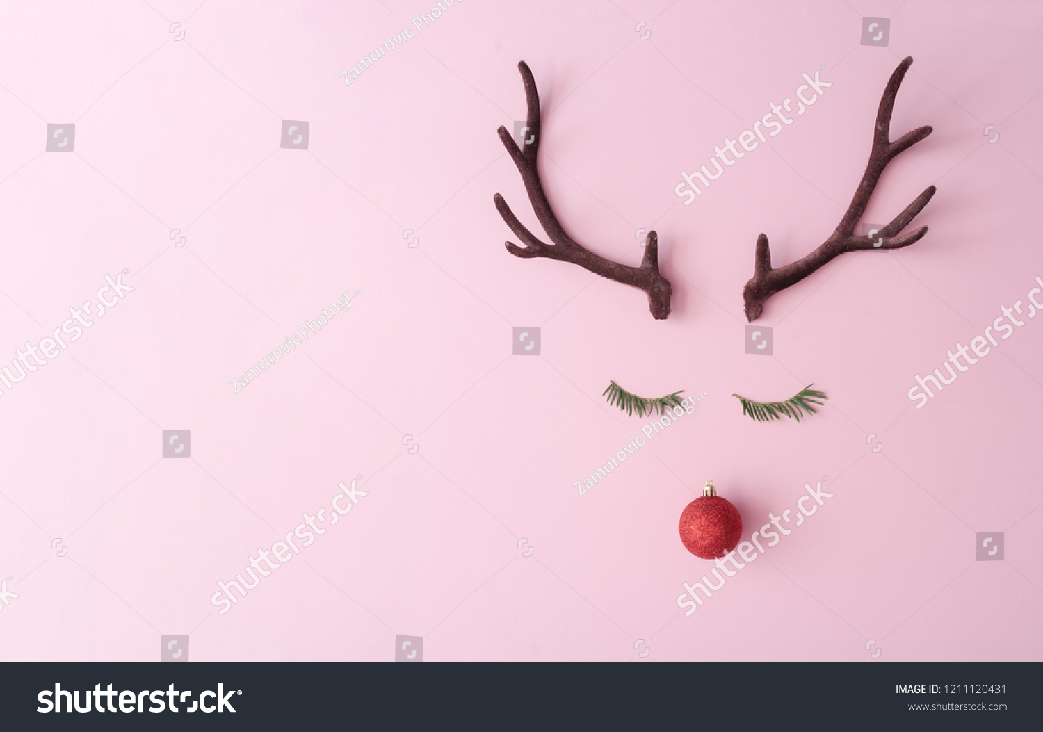 Christmas reindeer concept made of evergreen fir, red bauble decoration and antlers on pastel pink background. Minimal winter holidays idea. Flat lay top view composition. #1211120431