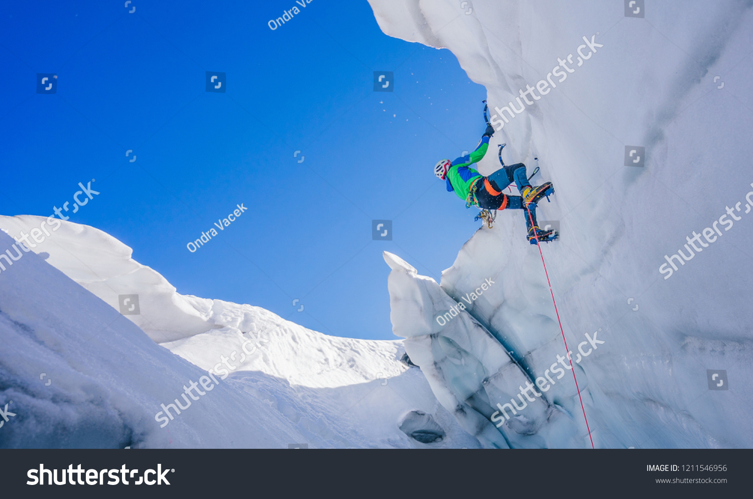Epic shot of an ice climber climbing on a wall of ice. Mountaineer, climber or alpinist on an adventure extreme ascent with ice axe and crampons. Alpine extreme climbing on a serac or creavasse. #1211546956