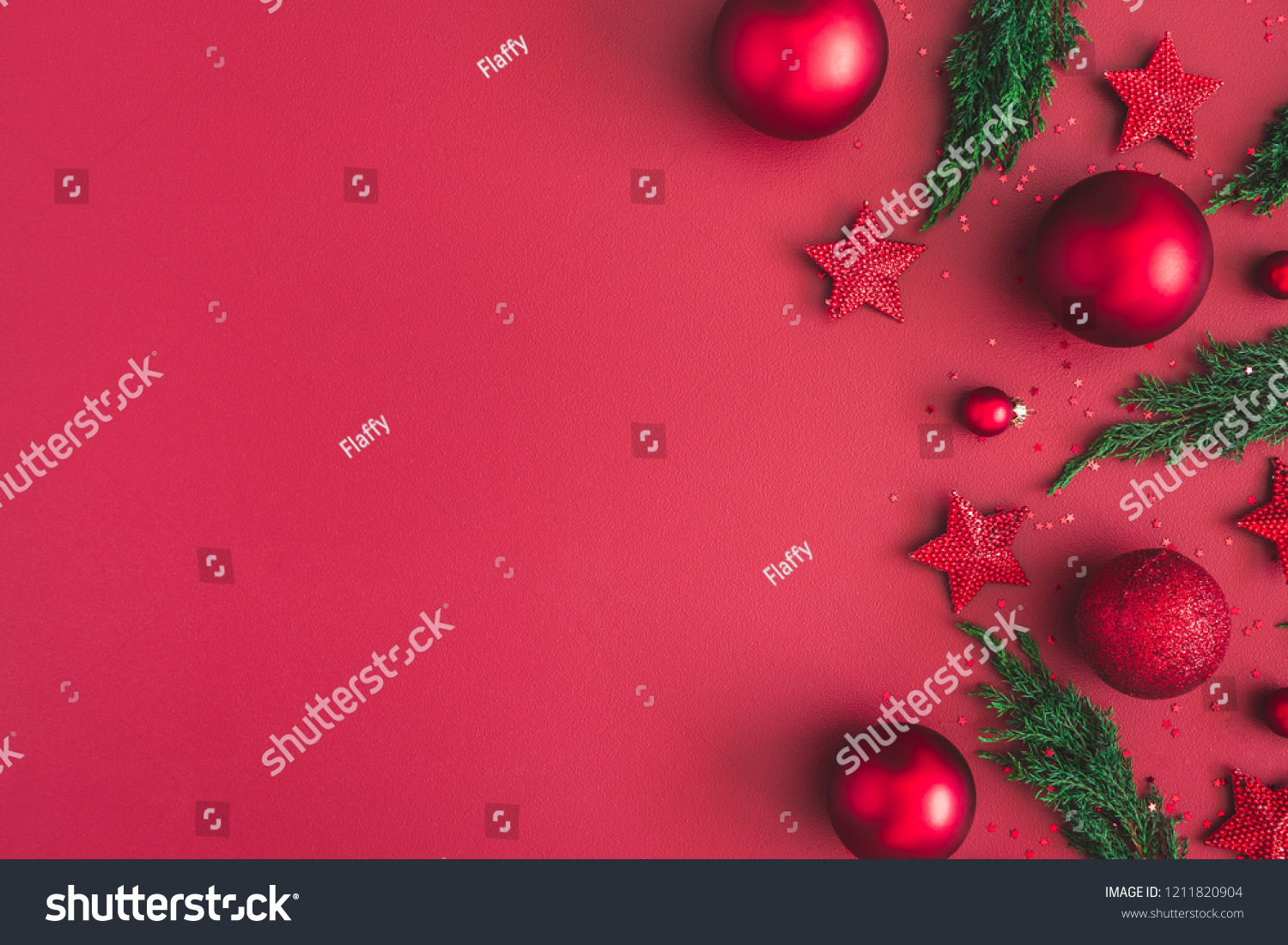 Christmas composition. Christmas red decorations, fir tree branches on red background. Flat lay, top view, copy space #1211820904