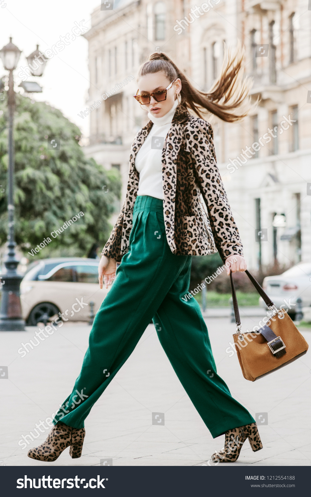 Outdoor full body fashion portrait of  fashionable woman wearing sunglasses, white turtleneck, leopard print blazer, boots, green trousers, holding brown suede bag, walking in street of european city #1212554188