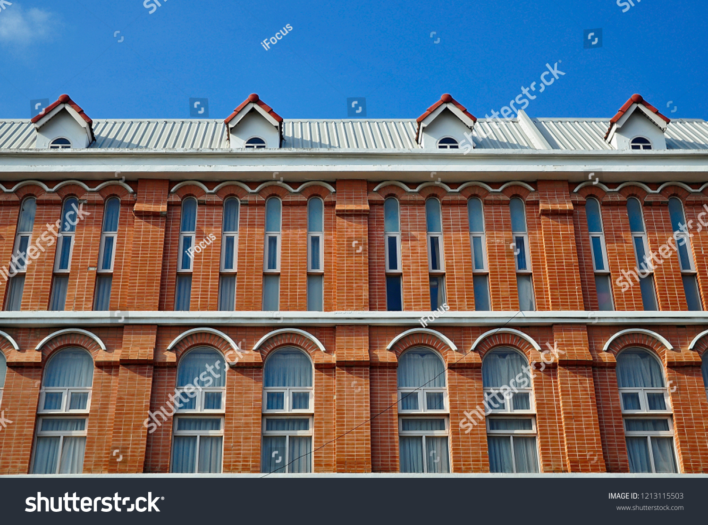 Shade of orange brick building contrast with blue sky
