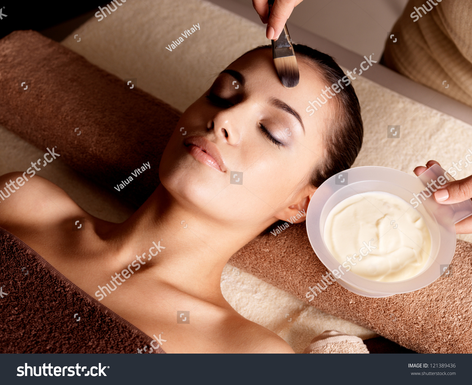 Spa therapy for young woman receiving facial mask at for Salon younga