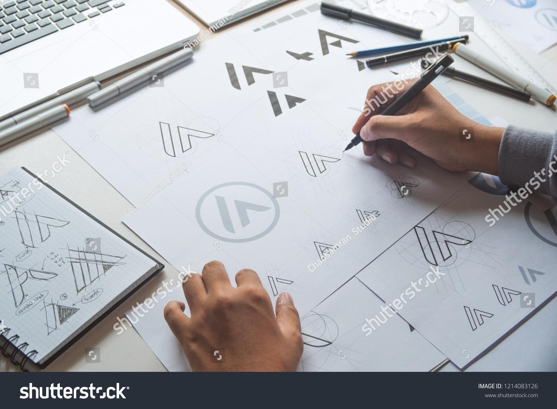 Graphic designer drawing sketch design creative Ideas draft Logo product trademark label brand artwork. Graphic designer studio Concept. #1214083126