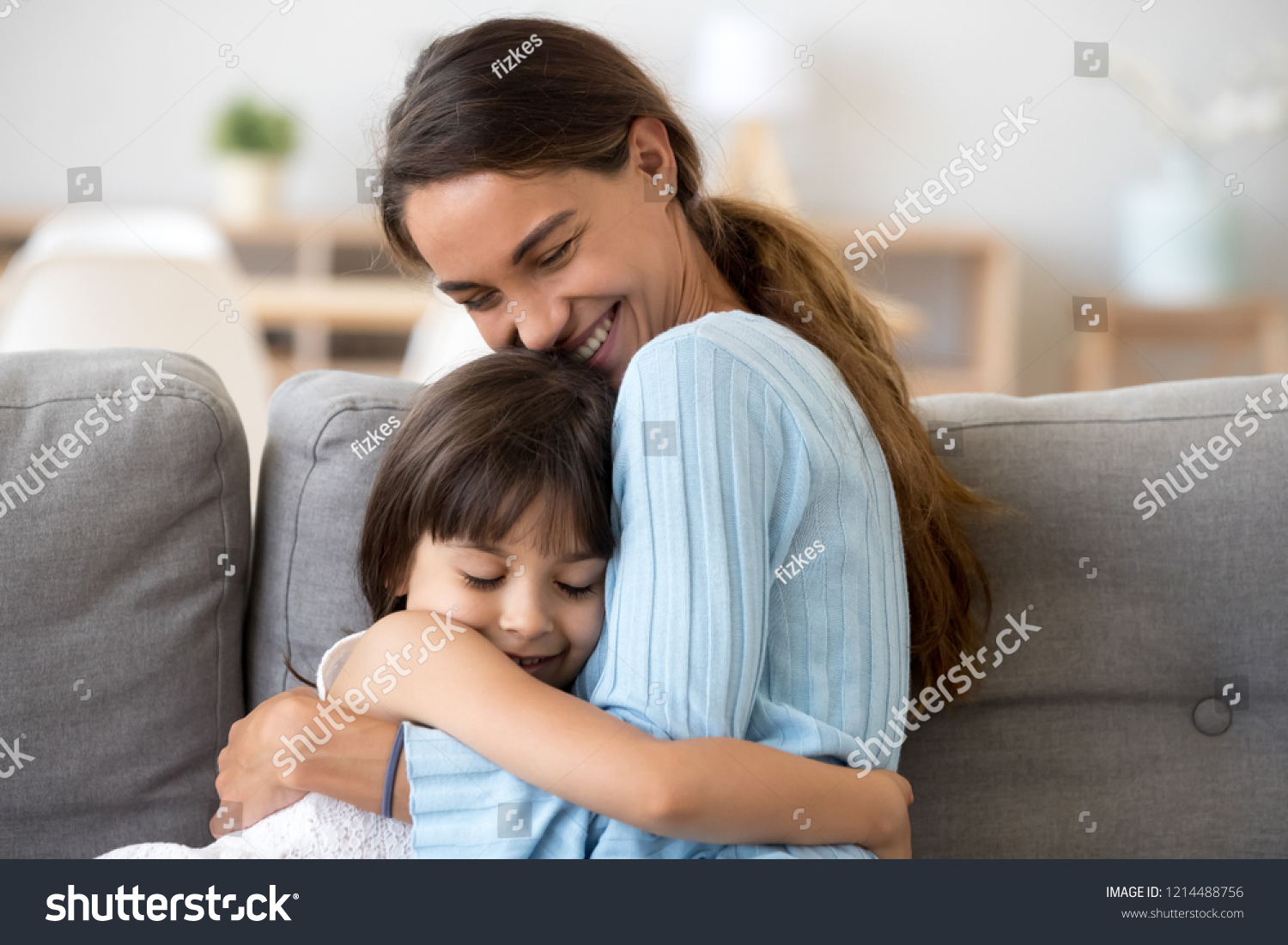 Mother and daughter with closed eyes sitting together on sofa at home  embracing feels happy and