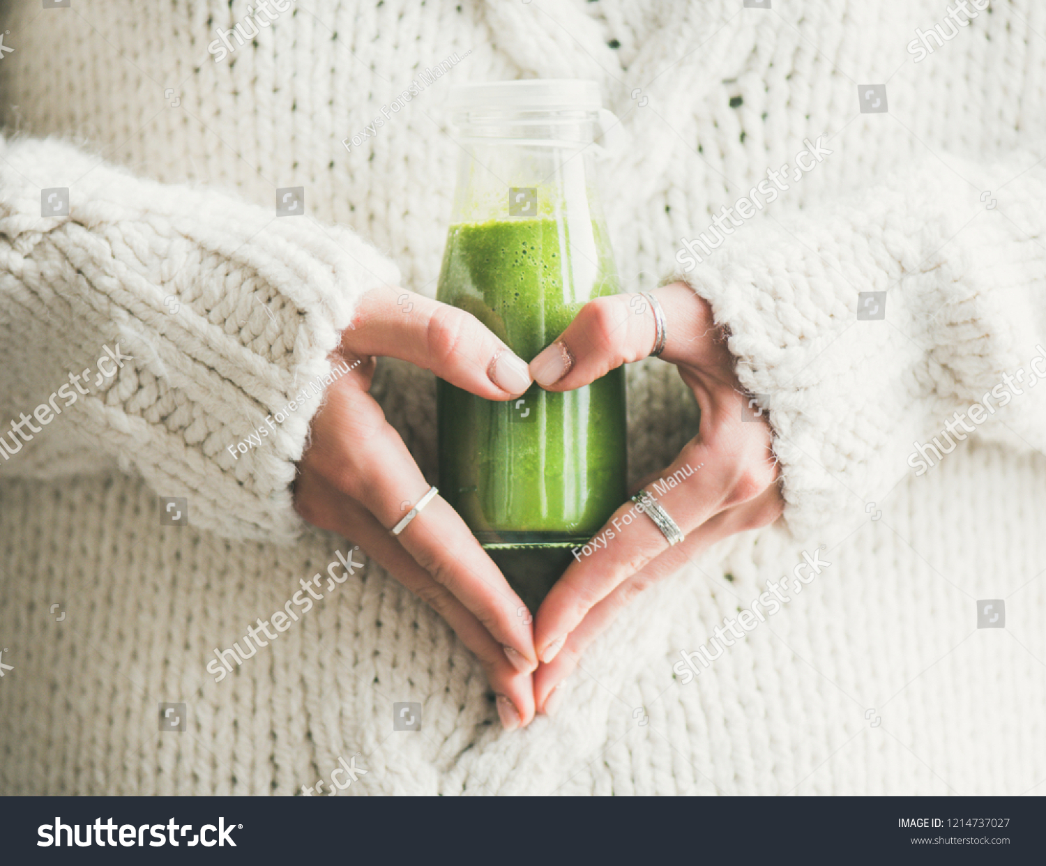 Winter seasonal smoothie drink detox. Female in woolen sweater holding bottle of green smoothie or juice making heart shape with her hands. Clean eating, weight loss, healthy dieting food concept #1214737027
