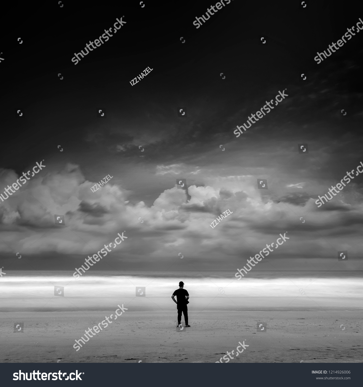 Lonely boy alone looking at the horizon near the beach during storm black and white