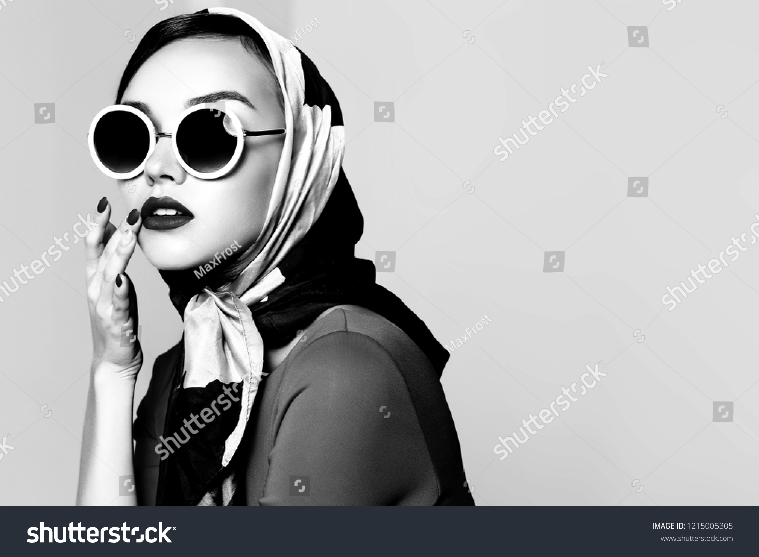 Young woman in retro style. Sunglasses and silk scarf. Sixties style fashion retro woman. Black and white image #1215005305