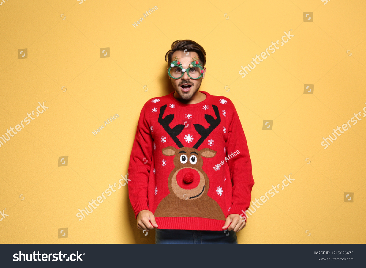Young man in Christmas sweater with party glasses on color background #1215026473