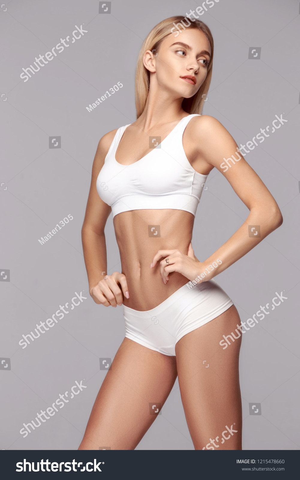 Perfect slim toned young body of the girl or fit woman at studio. The fitness, diet, sports, plastic surgery and aesthetic cosmetology concept. #1215478660