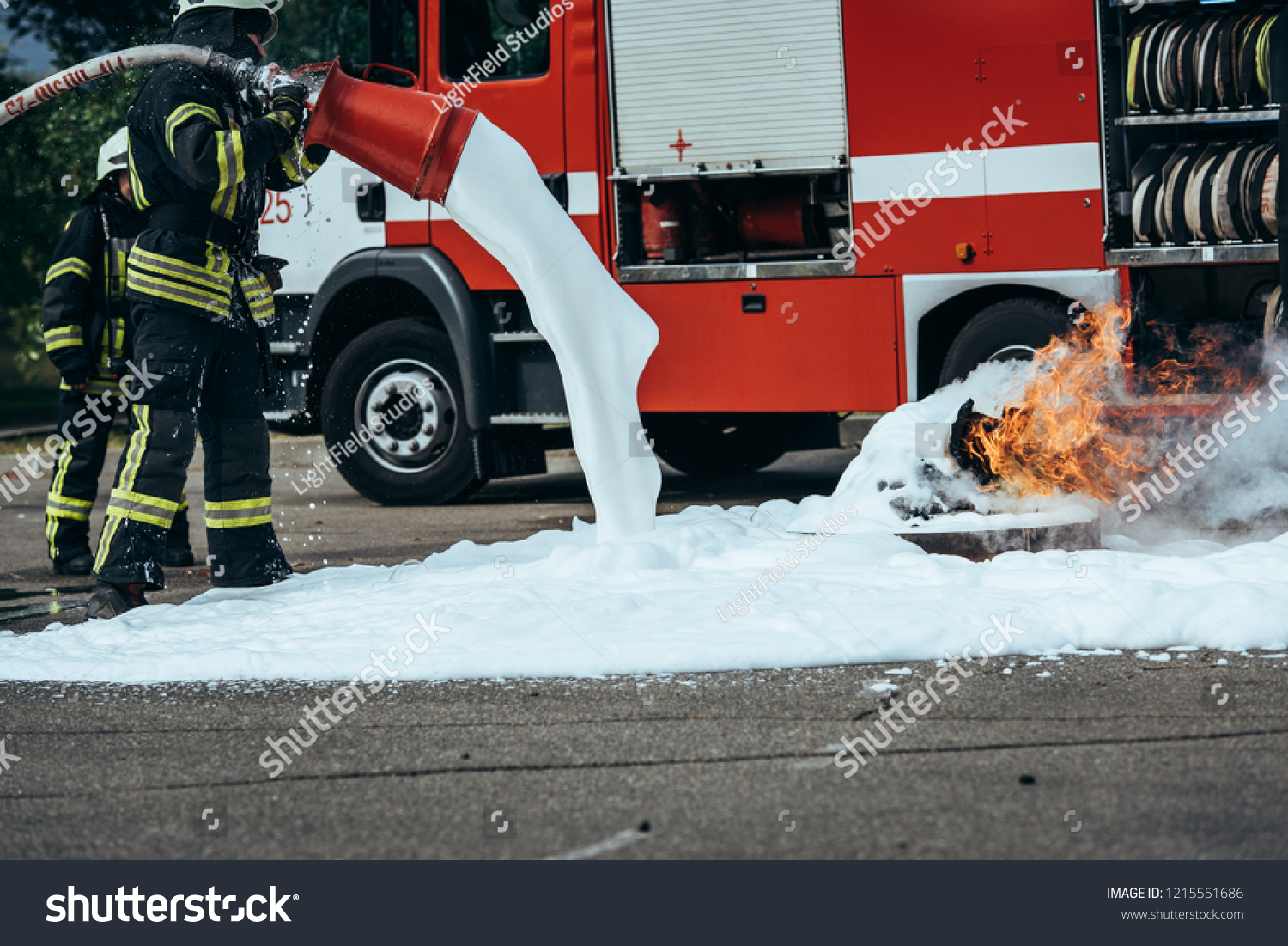 partial view of firefighter extinguishing fire with foam on street #1215551686