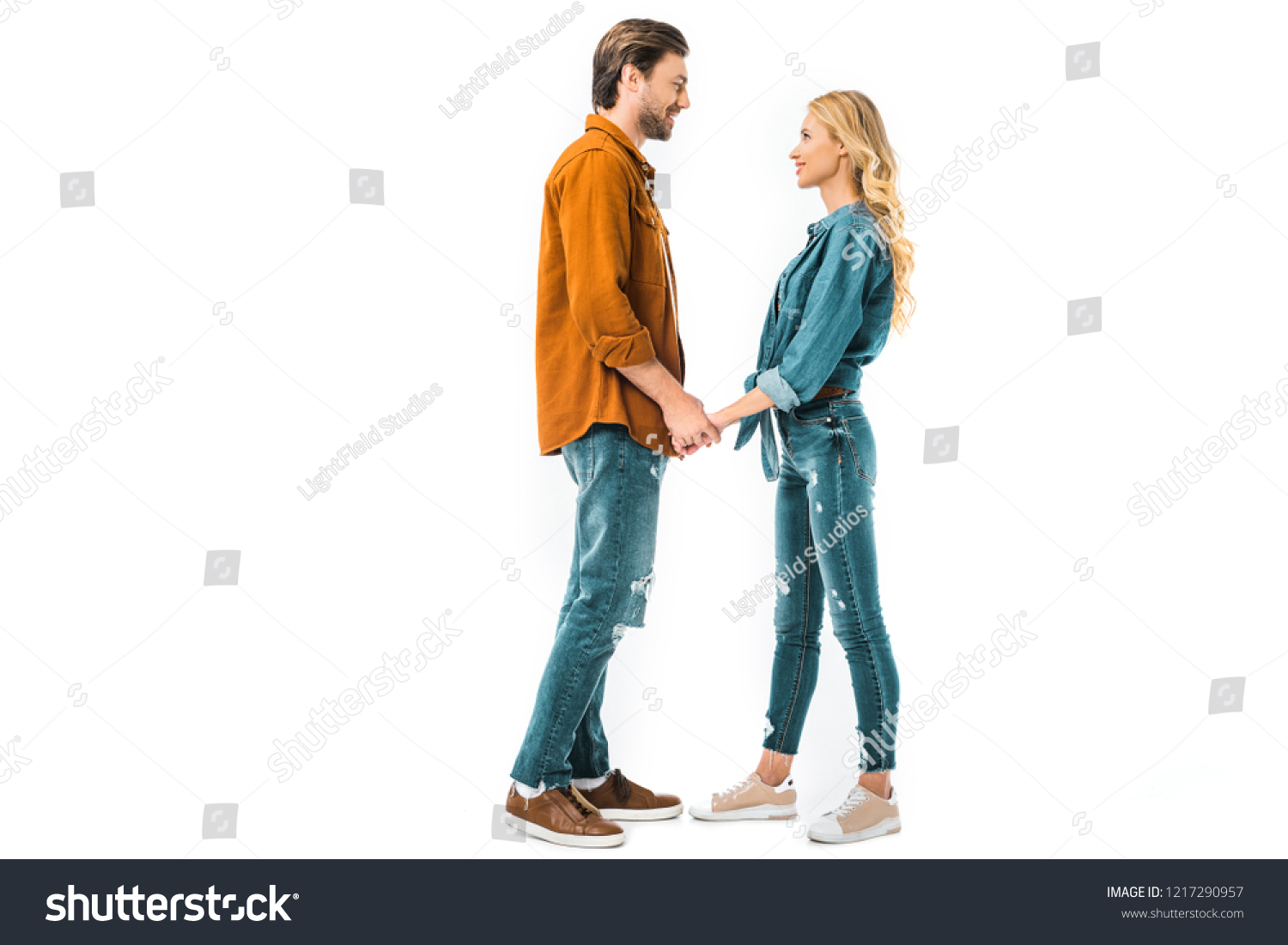 Side view of young couple holding hands and looking at each other isolated on white