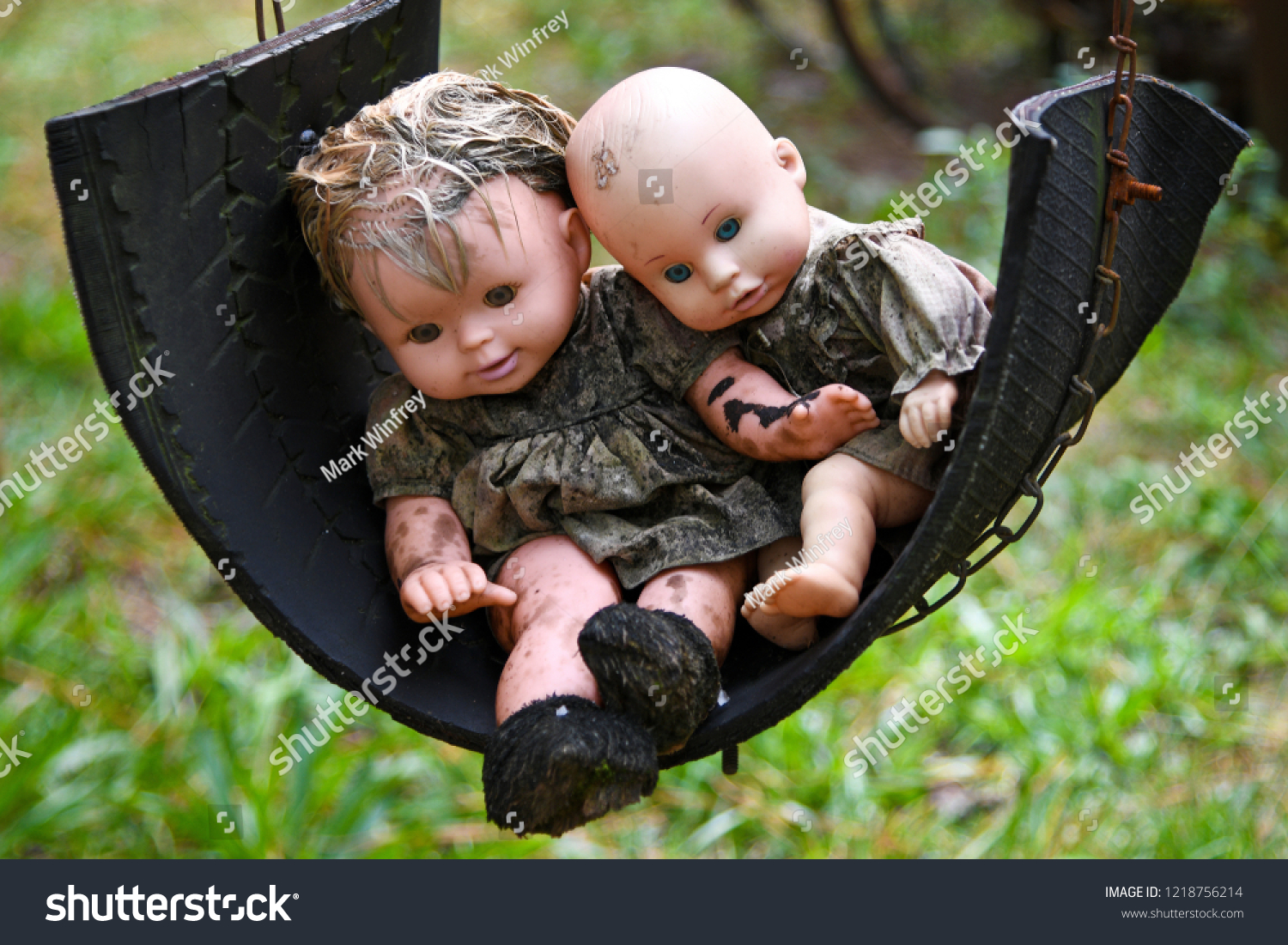 Two Creepy Grungy Old Baby Dolls Sitting in a Tire Swing