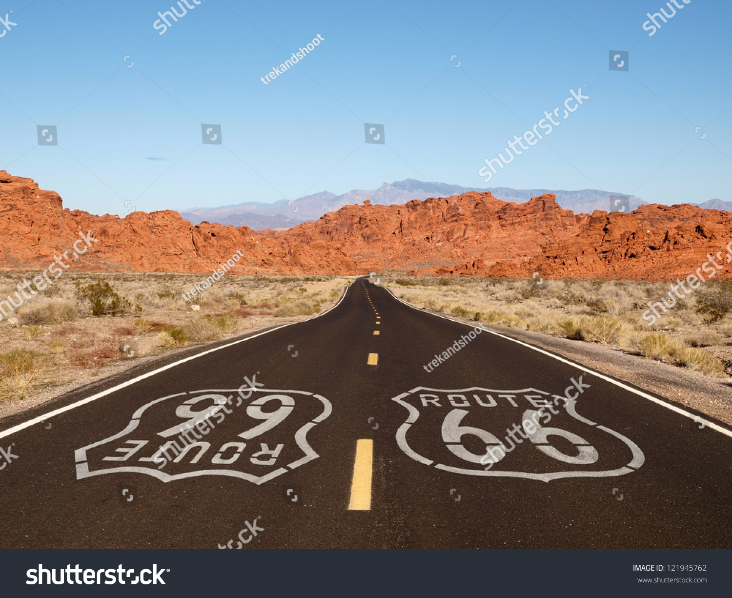 Route 66 pavement sign with Mojave desert red rock mountains. #121945762