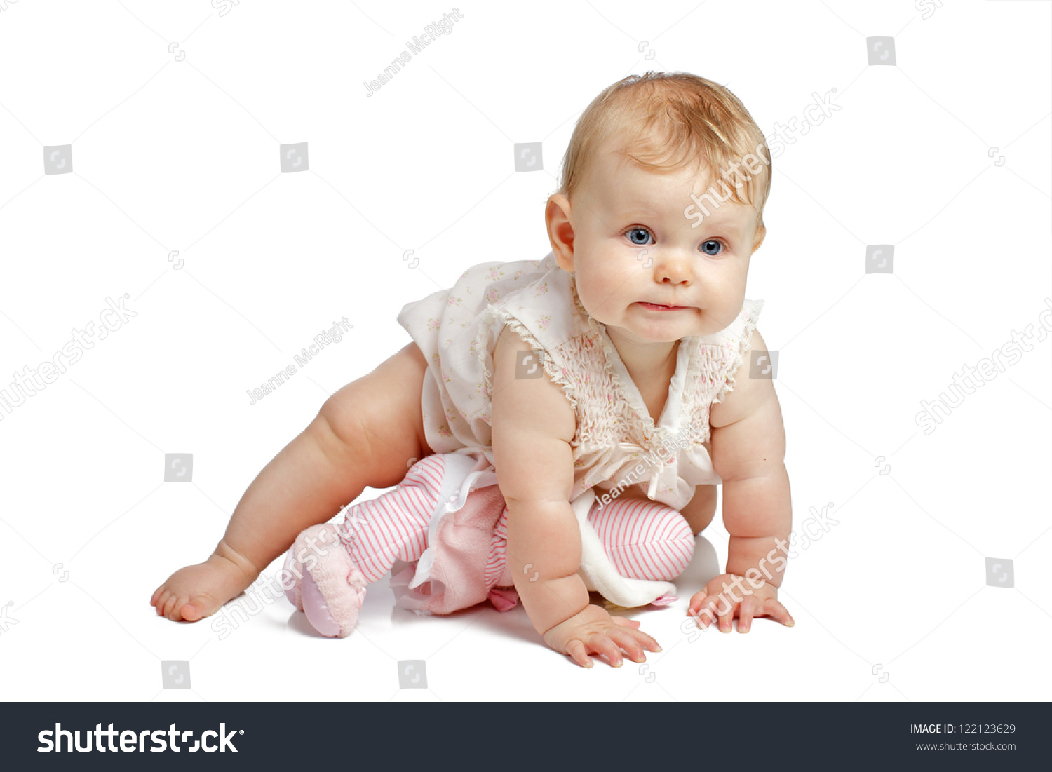 Active eight month old baby girl crawls with determined expression she wears a dainty sleeveless