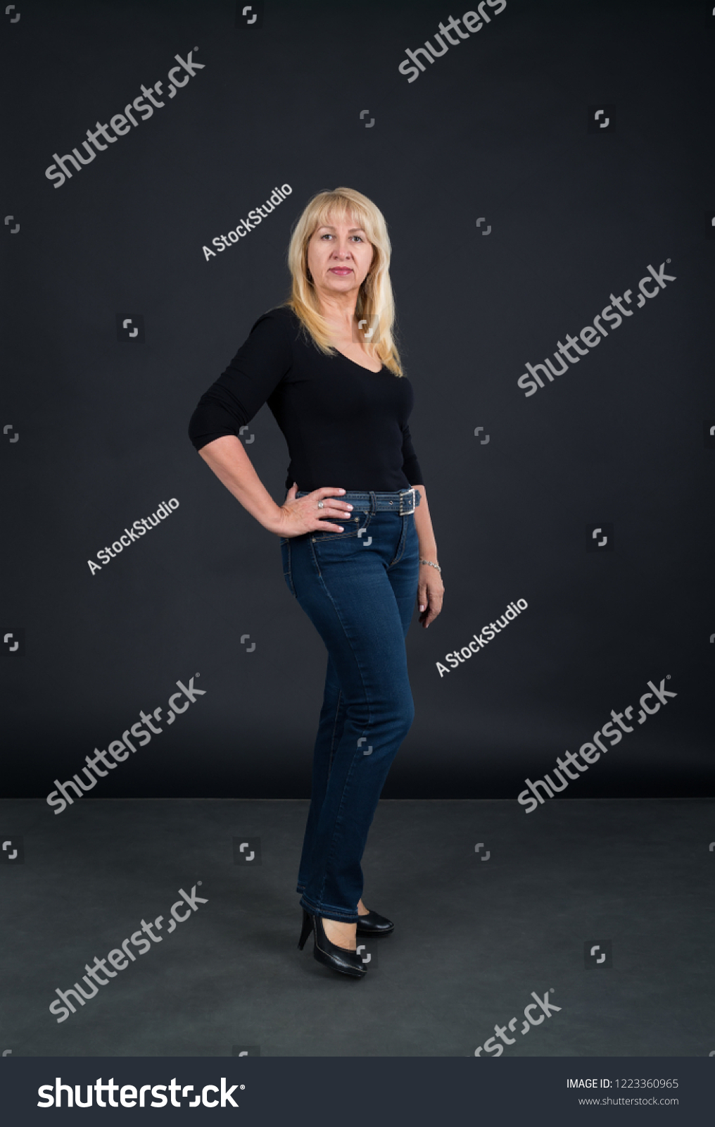 Mature woman 60 years old in full growth against a dark background.