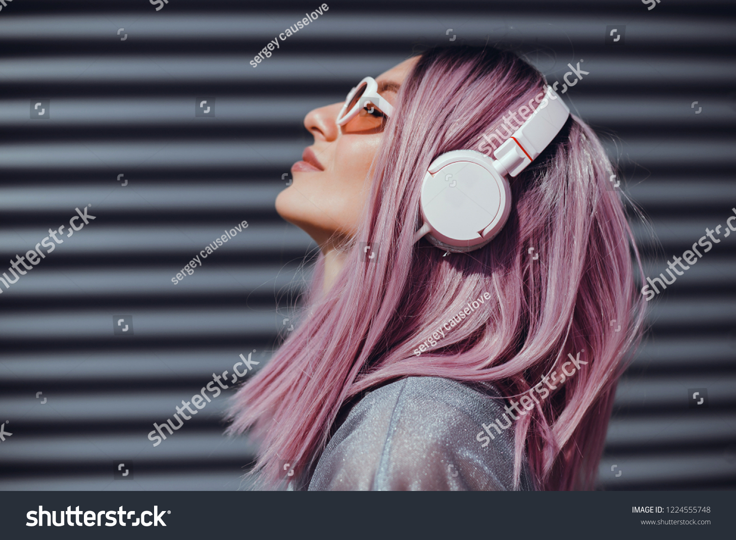 Beautiful young girl with purple pink hair listening to music on headphones, street style, outdoor portrait, hipster girl, music, mp3, Bali, beauty woman, sunglasses, orange color, concept #1224555748