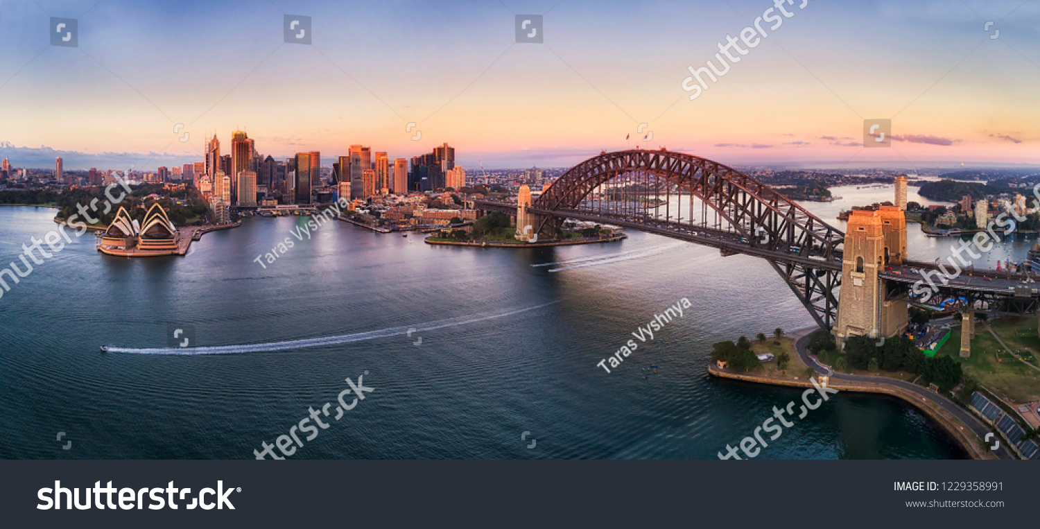 Colourful sky over Sydney city CBD high-rise towers at sunrise around Sydney harbour and the Sydney Harbour bridge in elevated aerial panorama. #1229358991