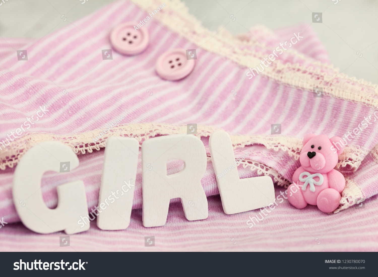 cute striped baby shirt in the background in soft pastel pink with word  girl for a