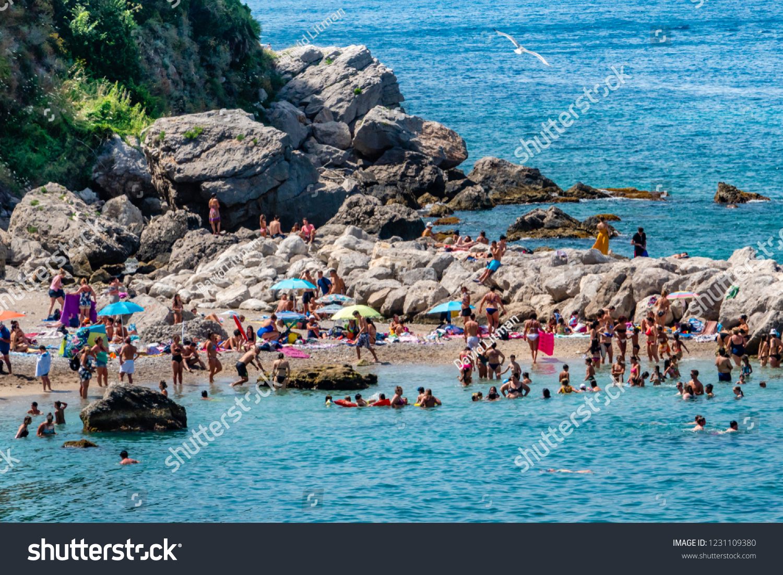 Capri, Italy - June 11, 2018; Locals and tourists enjoy a sunny day at the free Marina Grande Beach, on the island of Capri.